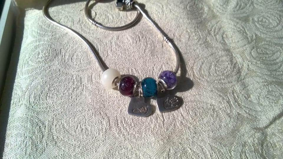 customer's own Pandora necklace with retired large style charms with wrapscraps and breastmilk