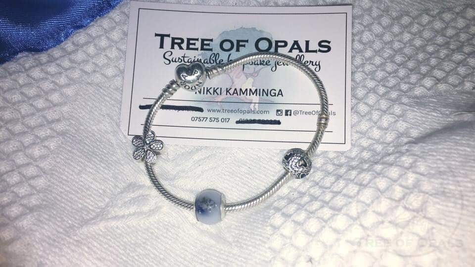 customer's own photo of Pandora bracelet with retired style small breastmilk charm with blue shimmer and lapis lazuli