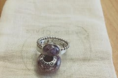 client's own photo of lavender cremation ash charm and rings with red garnet