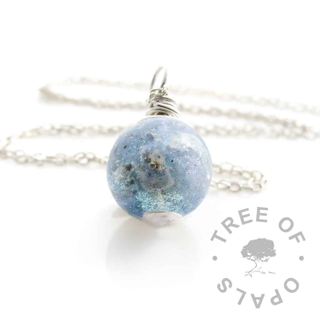cremation ash pearl with Aegean blue and unicorn white resin sparkle mixes (just choose Aegean blue and let us know in the comments if you'd like a paler blue). Hand wire wrapped with sterling EcoSilver, shown with the new style flat base