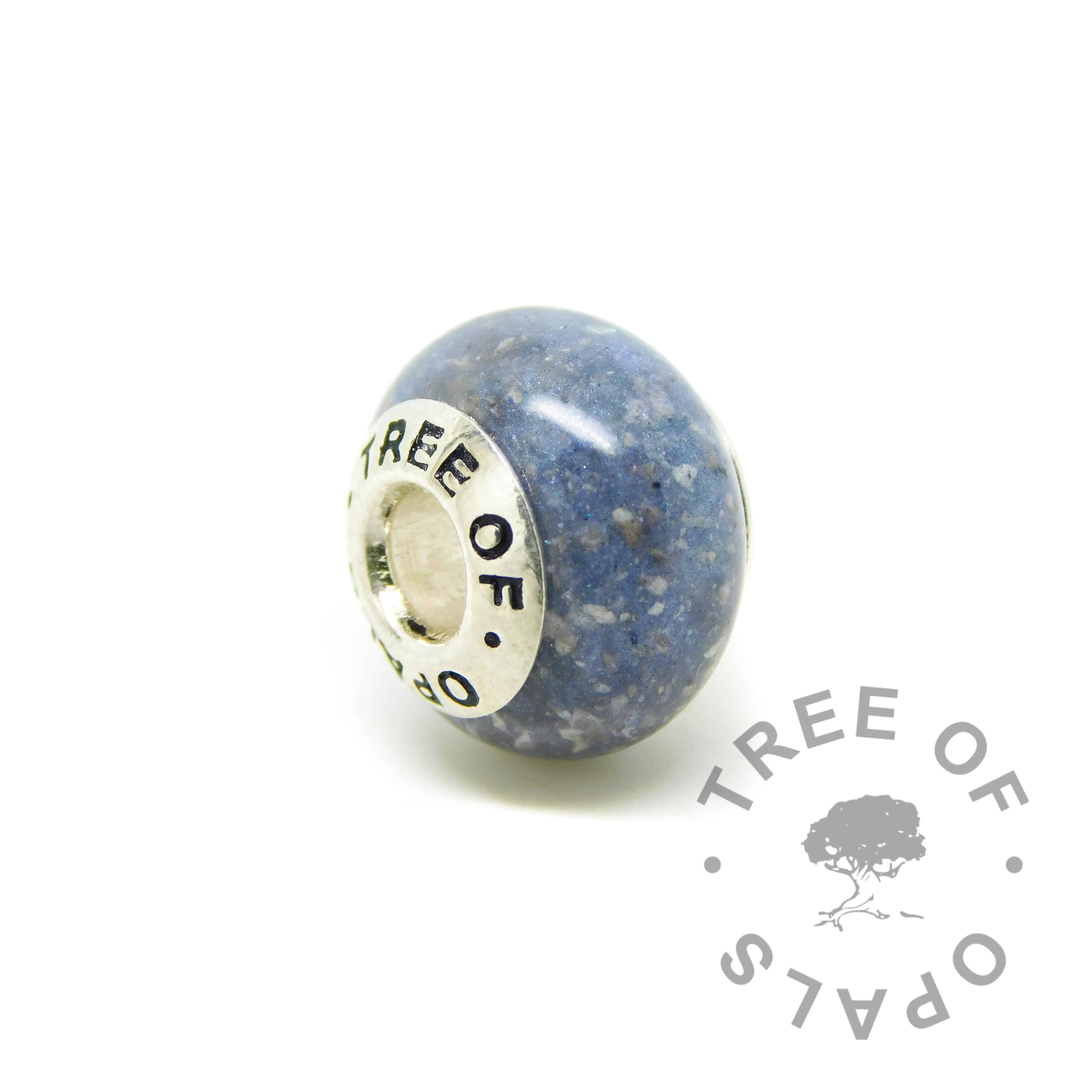 cremation ash charm. Cremation ashes with Aegean blue resin sparkle mix, no birthstone. Set with solid sterling silver Tree of Opals core for Chamilia and Pandora bracelets. Watermarked copyright image by Tree of Opals