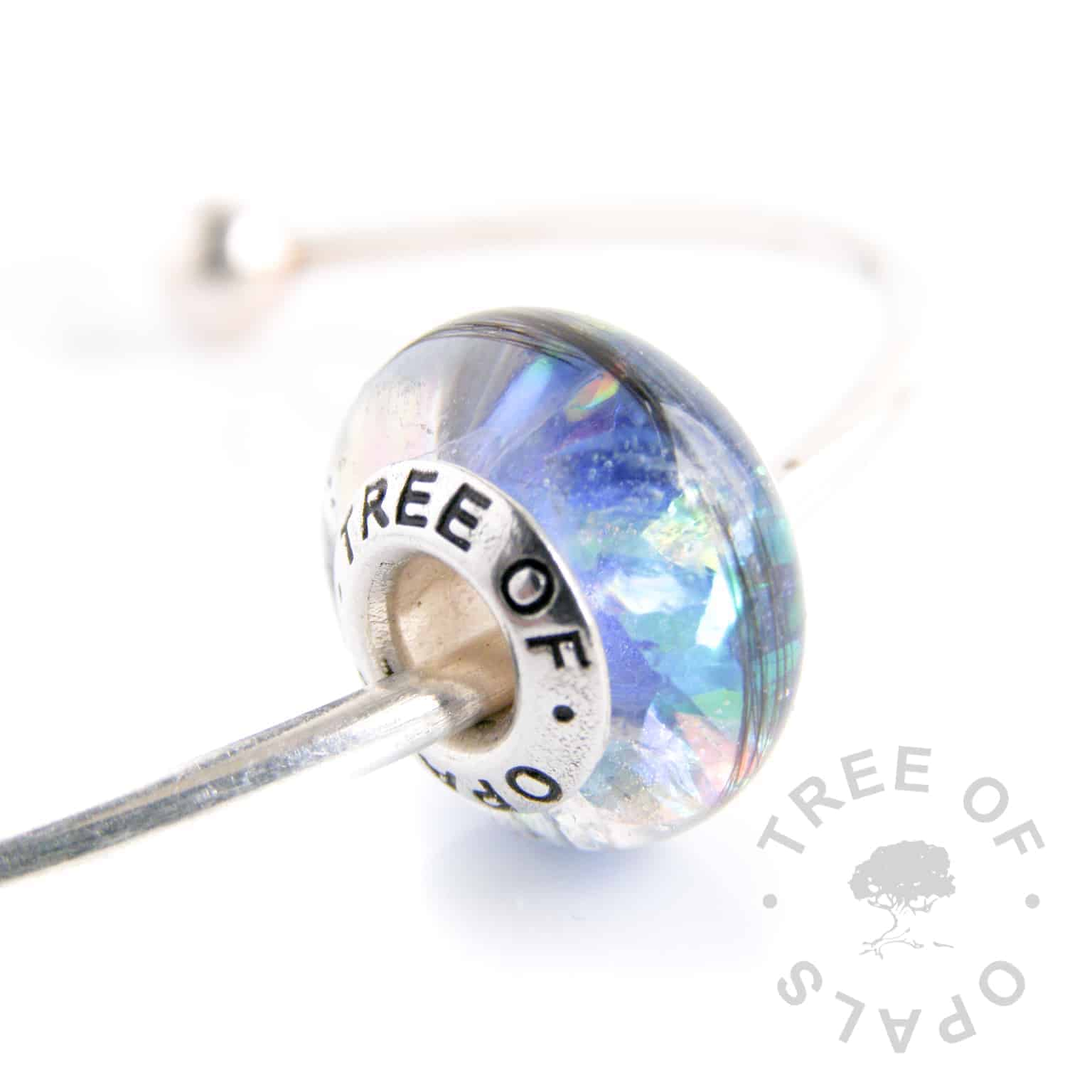 lock of hair charm bead blue opalescent flakes and Aegean blue shimmer core and solid sterling silver Tree of Opals signature core. Handmade with sterling silver by Tree of Opals