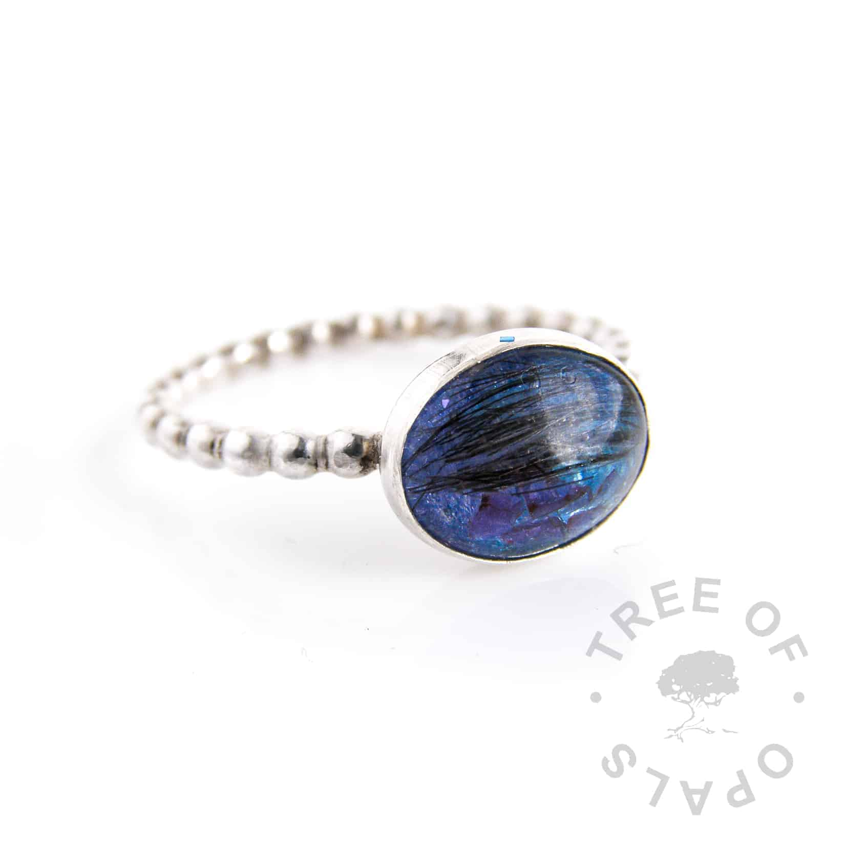 red garnet January birthstone lock of hair ring with various blue shimmers layered on the background in an oval bezel, bubble wire band. Handmade with sterling silver by Tree of Opals