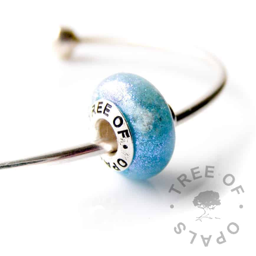 blue resin cremation ash charm with blue mermaid glitter shown on our torque bangle