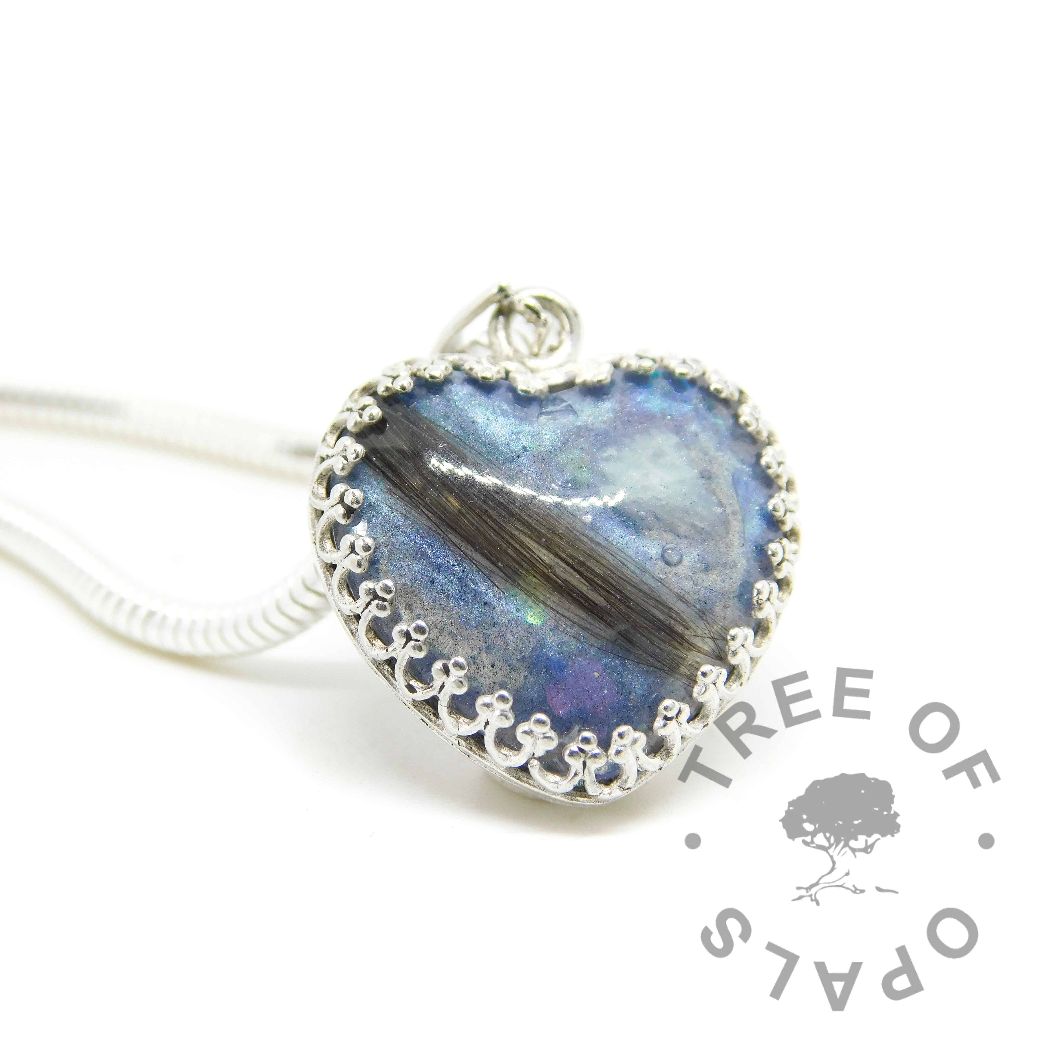 lock of hair heart necklace with aquamarine March birthstone and Aegean blue resin sparkle mix. 18mm heart with solid sterling silver crown point setting. Shown with wide snake chain upgrade. Copyright watermarked image