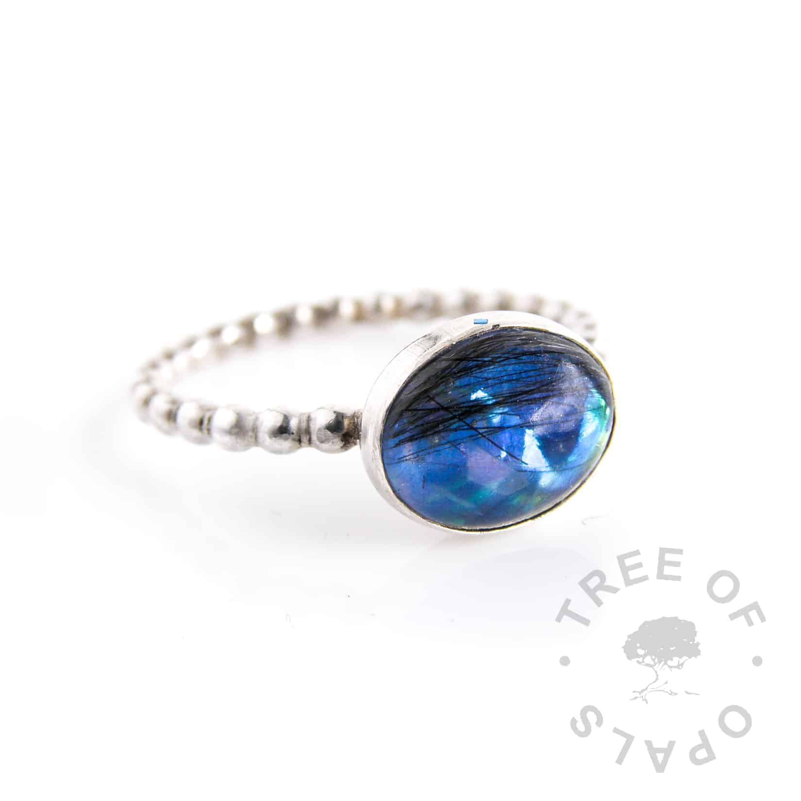 lock of hair ring blue opalescent flakes and Aegean blue shimmer background in an oval bezel, bubble wire band. Handmade with sterling silver by Tree of Opals