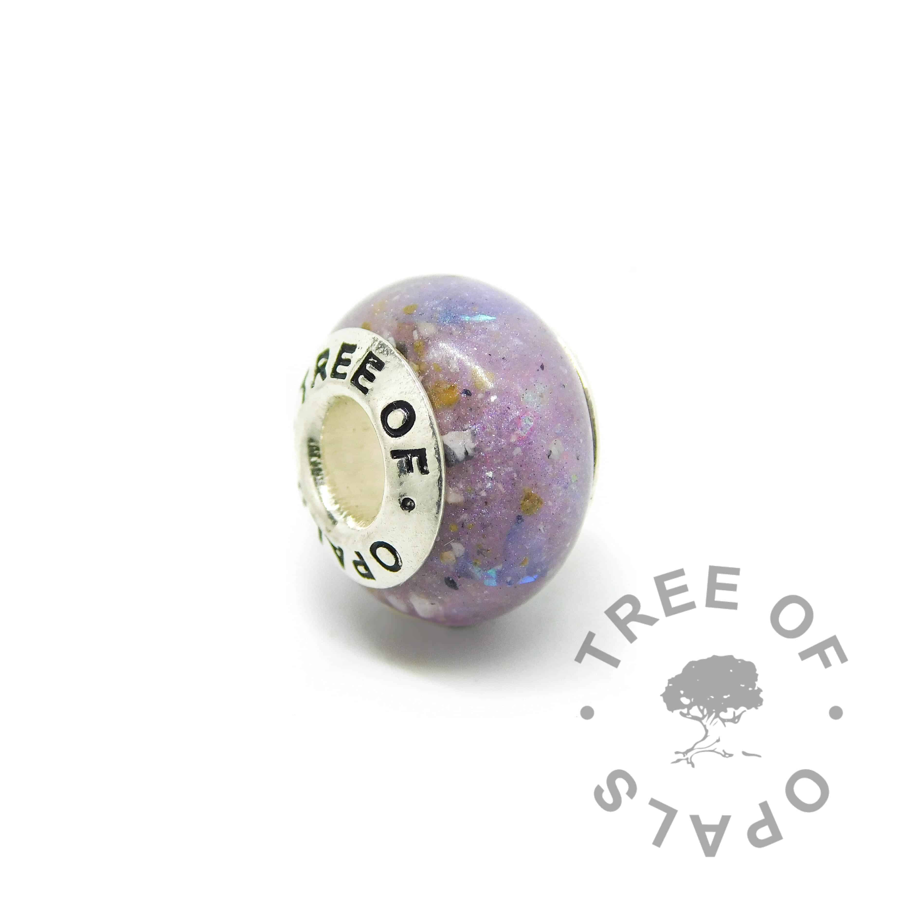 cremation ash charm with orchid purple resin sparkle mix, genuine diamond powder April birthstone. Solid sterling silver Tree of Opals signature core (925 stamped on the back). Watermarked copyright Tree of Opals memorial jewellery image