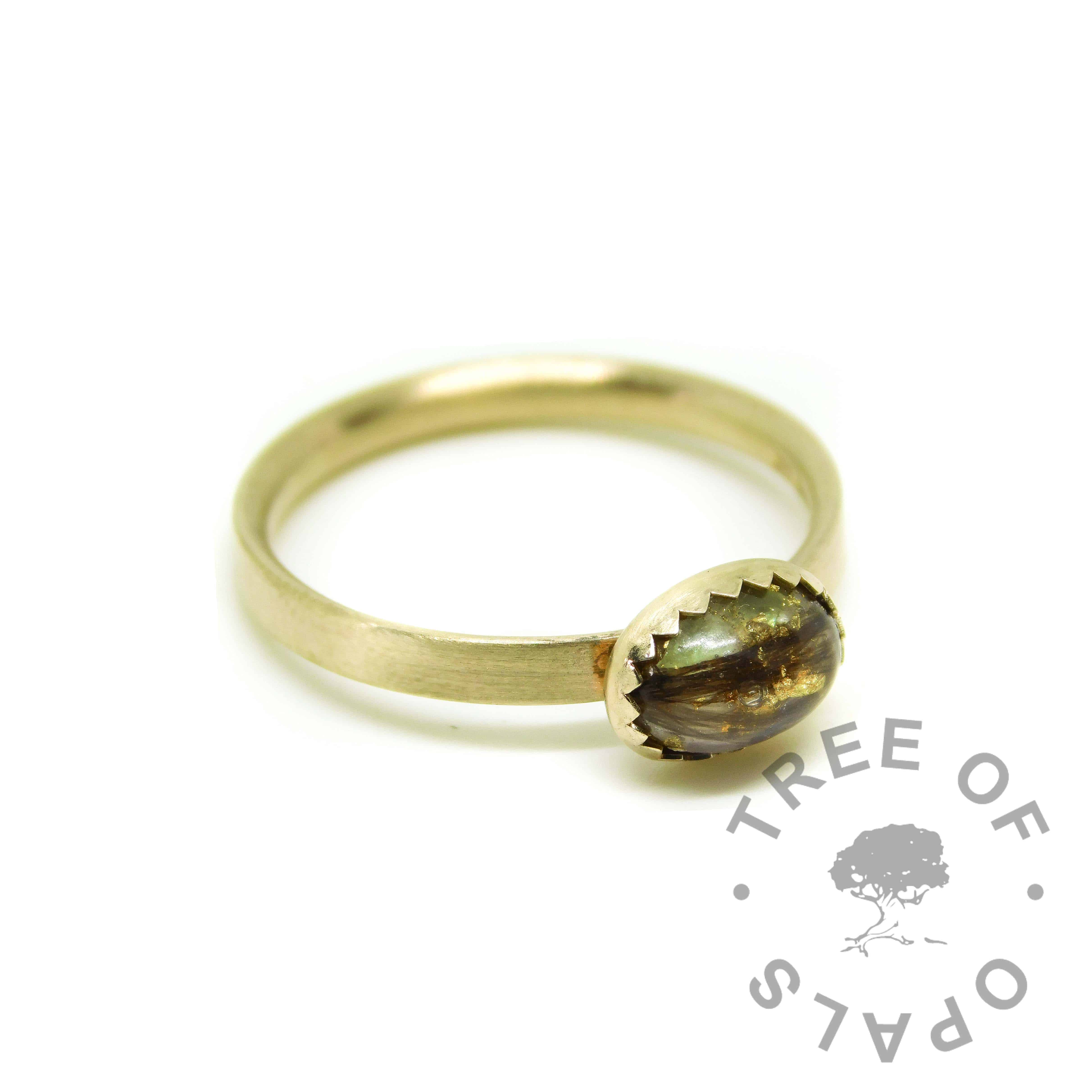 Solid gold lock of hair ring with unicorn white resin sparkle mix and August birthstone rough natural peridot, and gold leaf. Brushed band gold ring solid 14ct gold with serrated setting