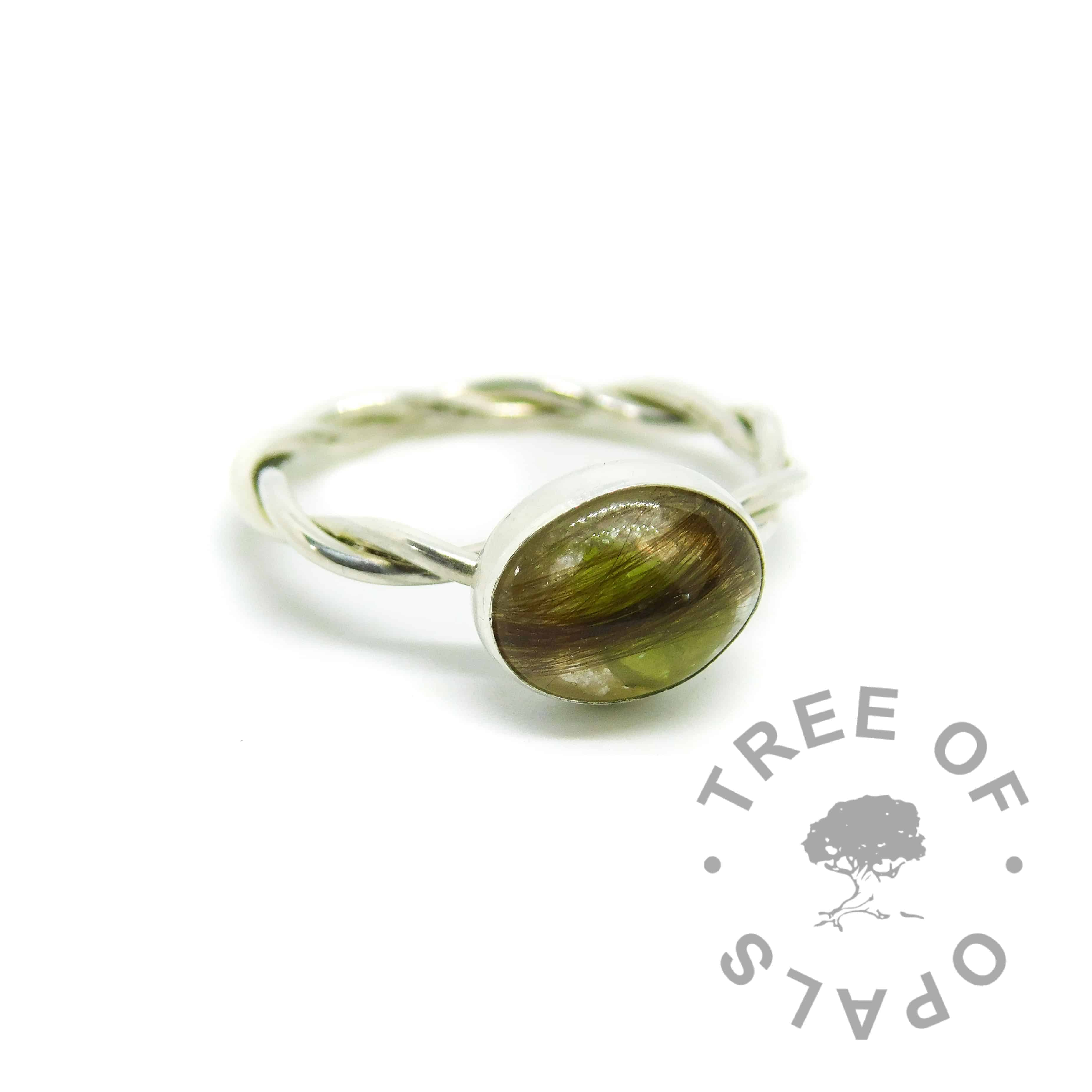 lock of ring with unicorn white resin sparkle mix, large rough natural peridot August birthstone. Handmade twisted band EcoSilver ring shank, 10x8mm bezel cup. Watermarked copyright Tree of Opals memorial jewellery image