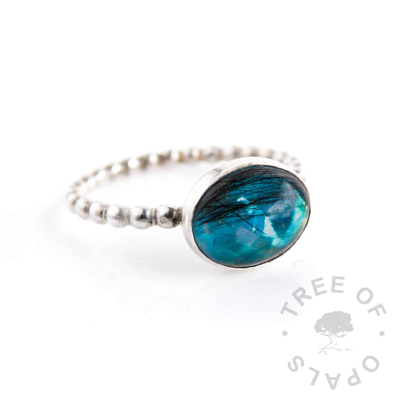 lock of hair ring with teal opalescent flakes background on a bubble wire solid silver band and 10x8mm oval cabochon