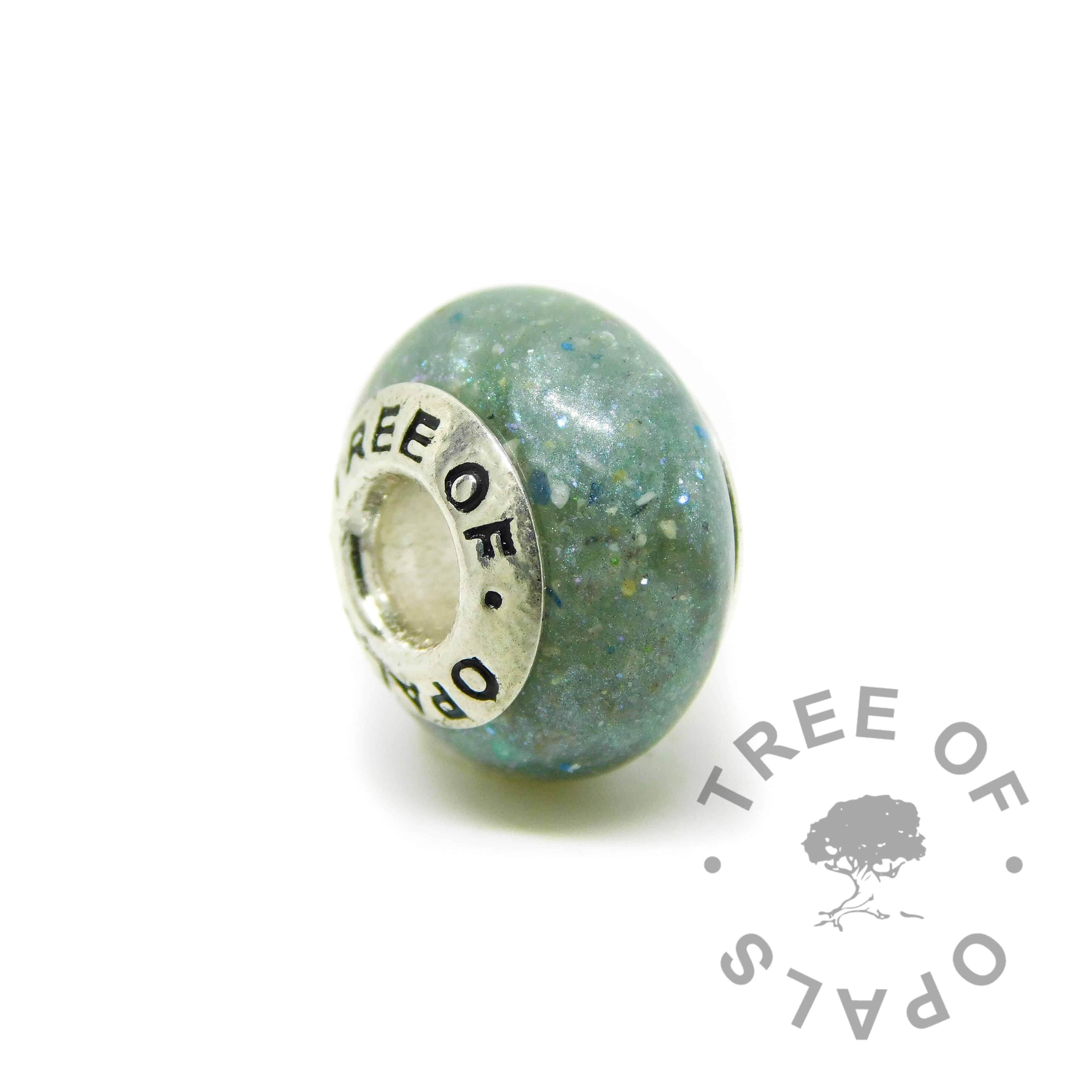 Cremation ash charm. Cremation ashes with mermaid teal resin sparkle mix,no birthstone. Set with solid sterling silver Tree of Opals core for Chamilia and Pandora bracelets. Watermarked copyright image by Tree of Opals