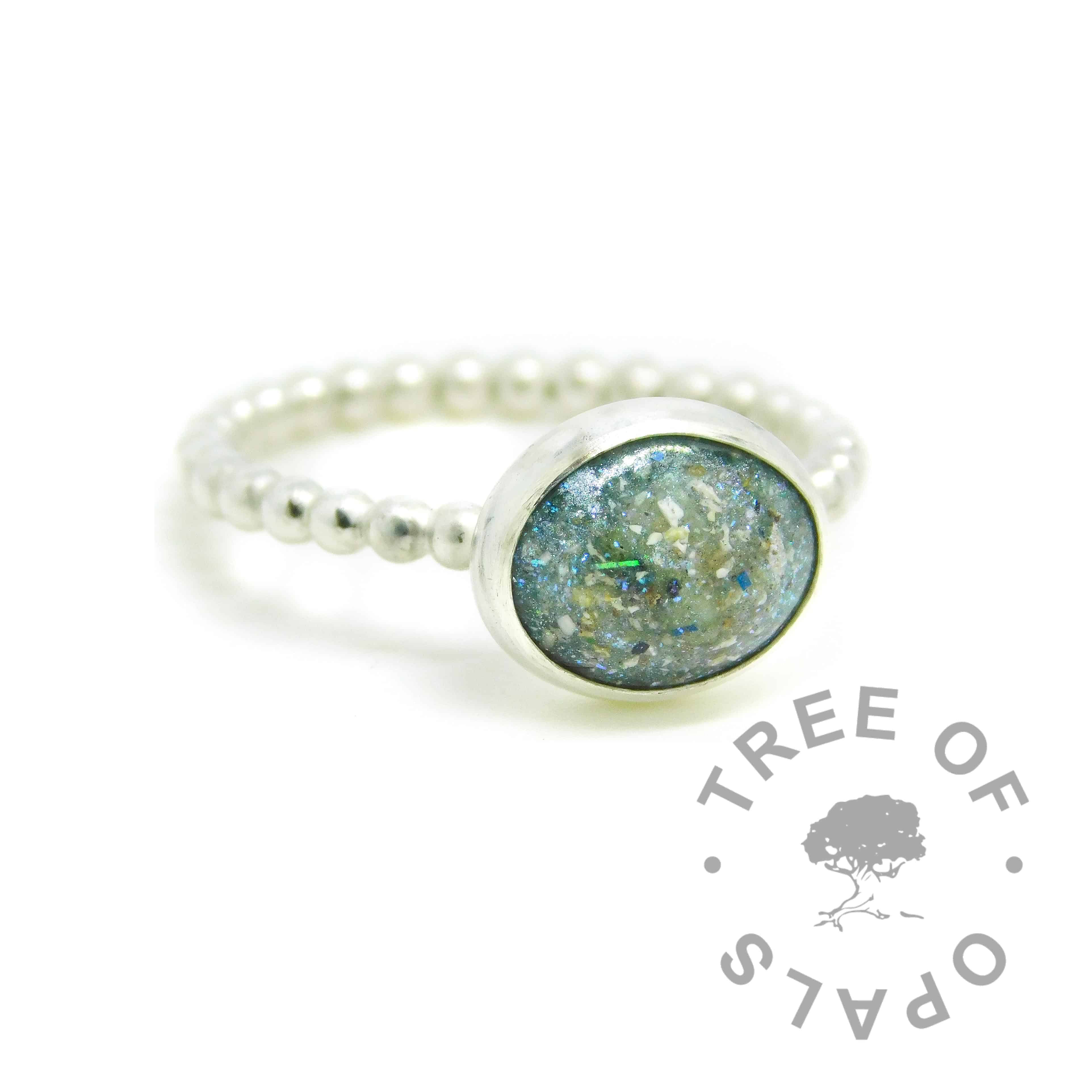 teal cremation ash ring on a handmade Argentium silver bubble wire band stacking ring. 10x8mm cabochon with cremation ashes and mermaid teal custom resin sparkle mix.
