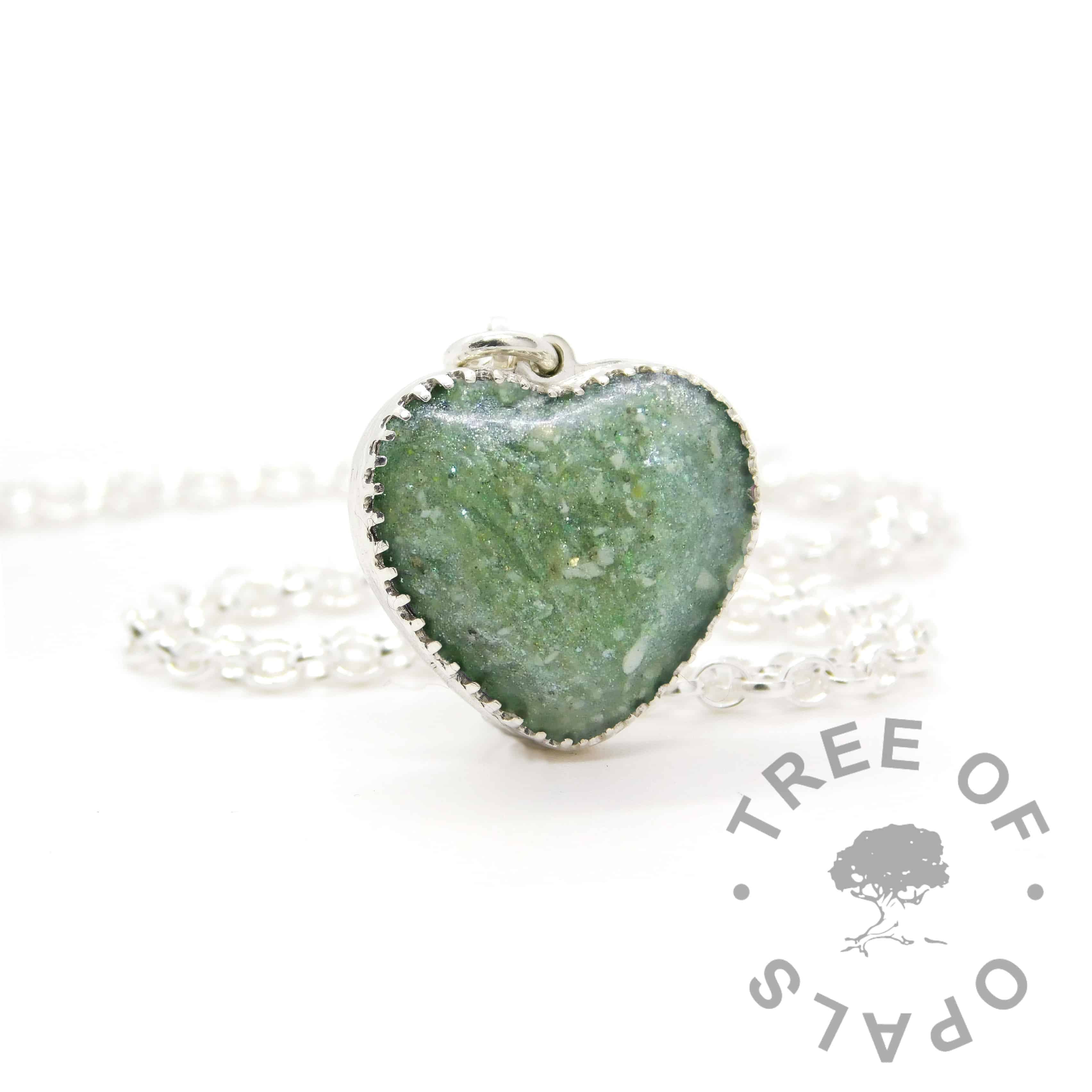 New style heart necklace setting with scalloped edge. Mermaid teal resin sparkle mix, cremation ashes (naturally brown colour ashes), shown with a medium classic chain upgrade (mockup of new setting)