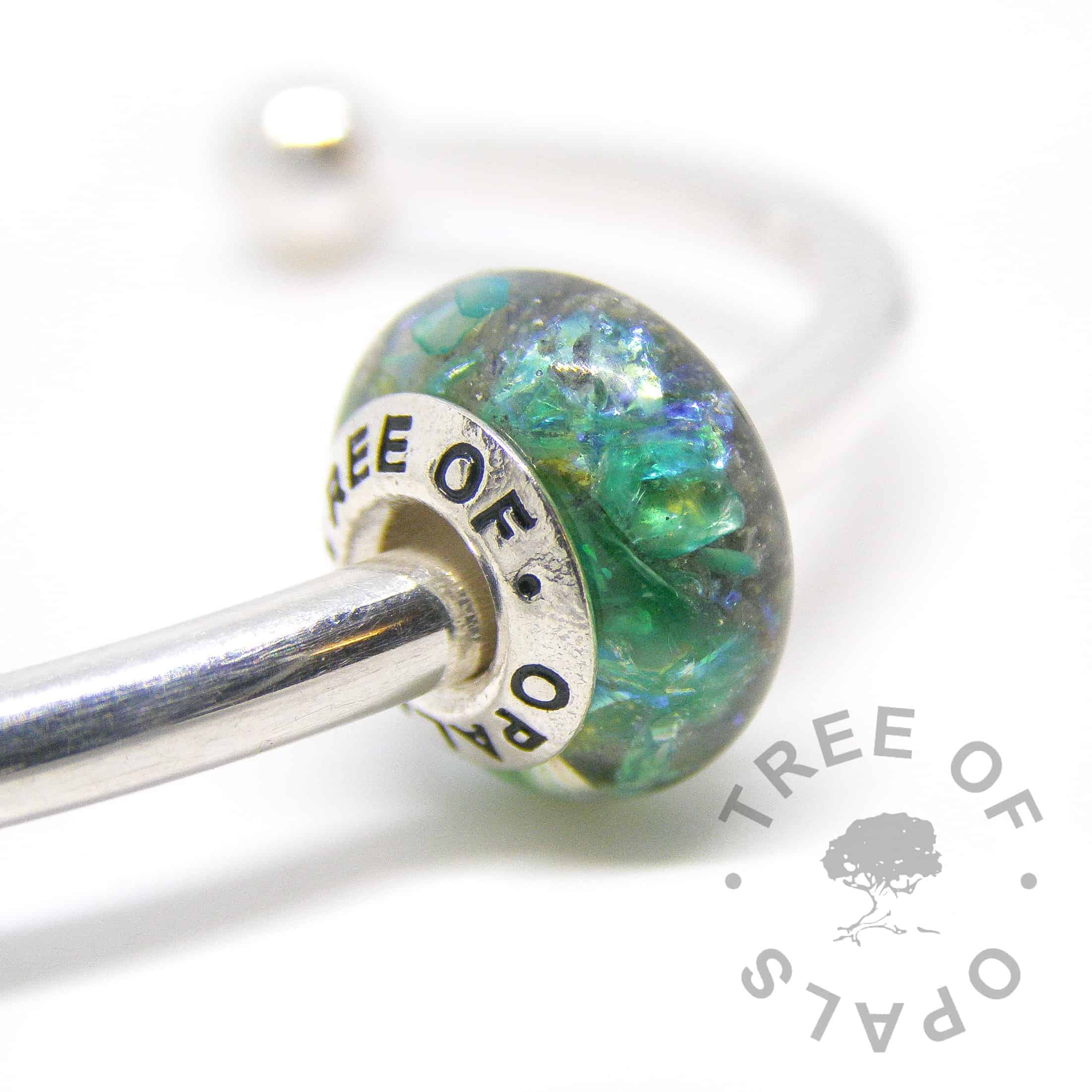 cremation ashes bead in resin, green opalescent and peridot August birthstone with a solid sterling silver Tree of Opals branded core cremation ash charm