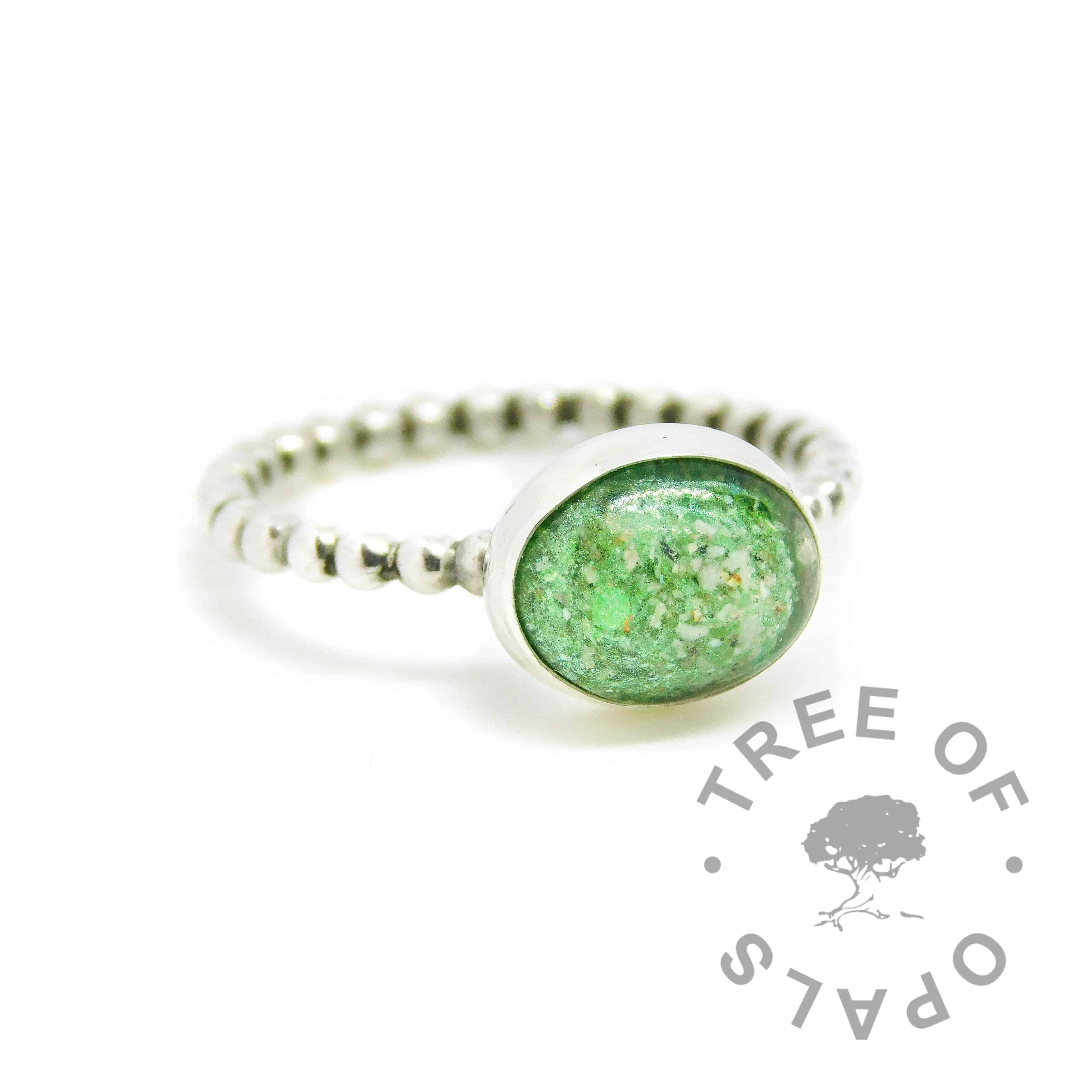 Cremation ash ring with basilisk green resin sparkle mix, no birthstone. 2mm wide bubble wire ring band handformed with solid 935 Argentium silver (slightly purer than sterling silver), and 10x8mm pure silver bezel cup. Watermarked copyright Tree of Opals memorial jewellery image