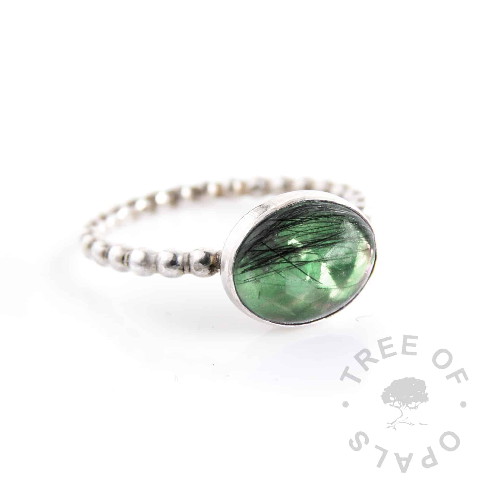 lock of hair ring with dark green opalescent flakes background on a bubble wire solid silver band and 10x8mm oval cabochon