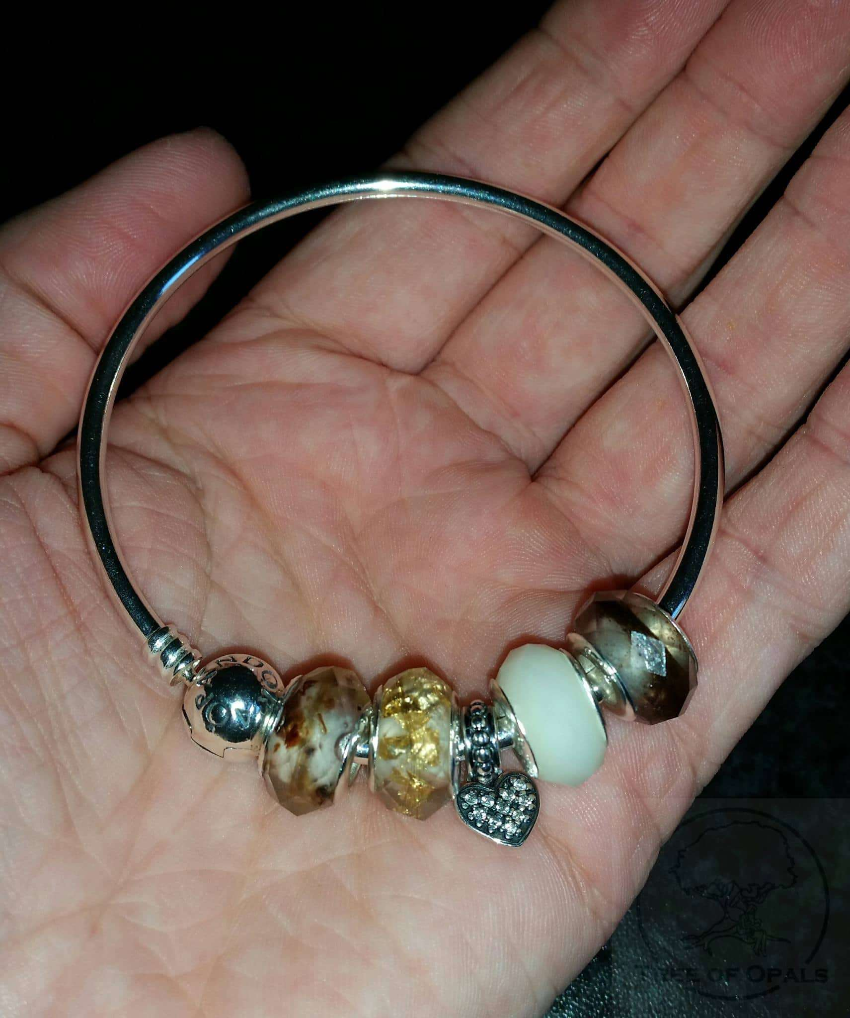customer's own Pandora bracelet with umbilical cord lock of hair charms and breastmilk charm, retired faceted style