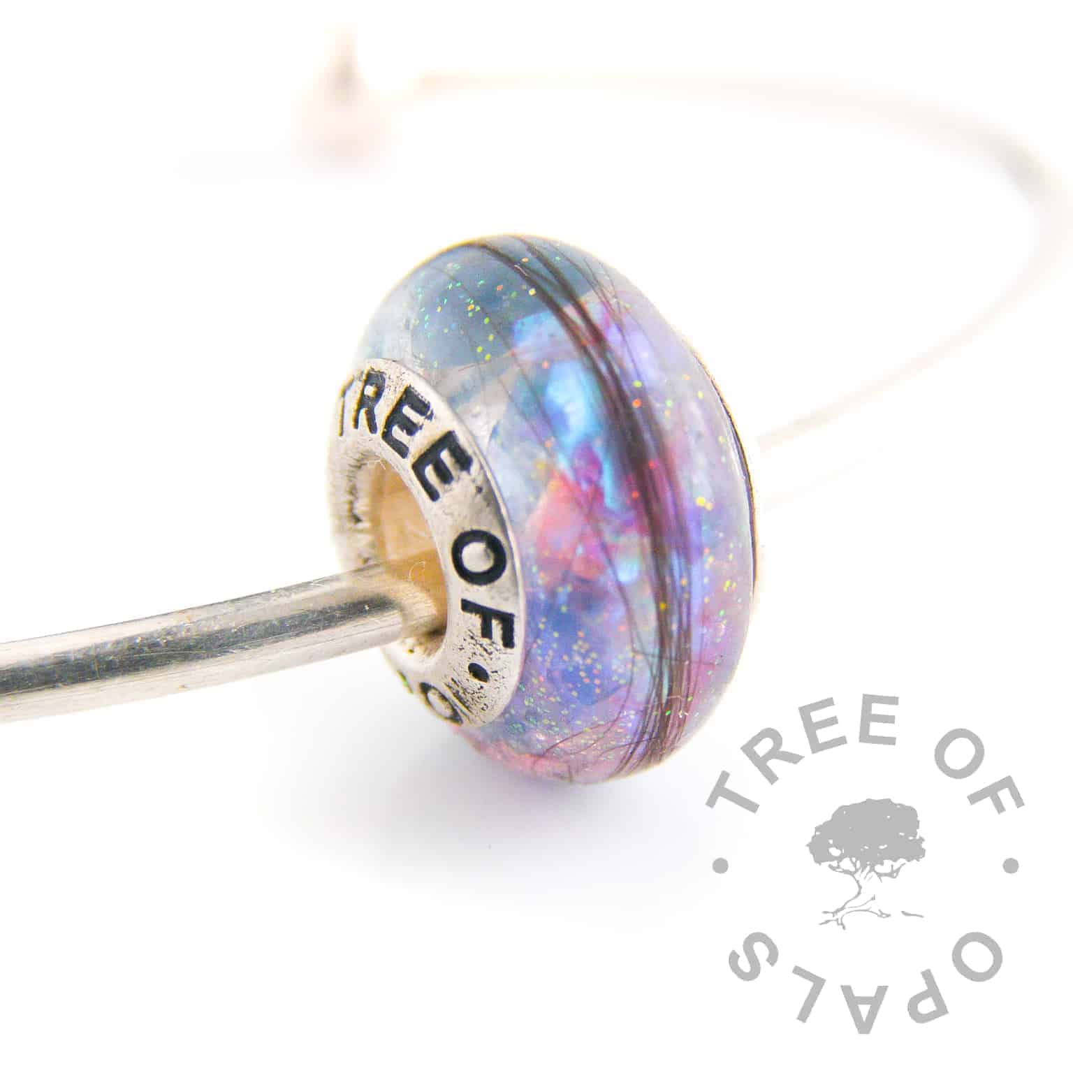 lock of hair charm bead blue topaz December birthstone and blue and pink sparkles opalescent flakes