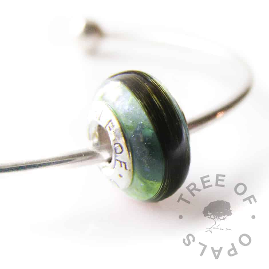 lock of hair charm with blue topaz and green opalescent flakes