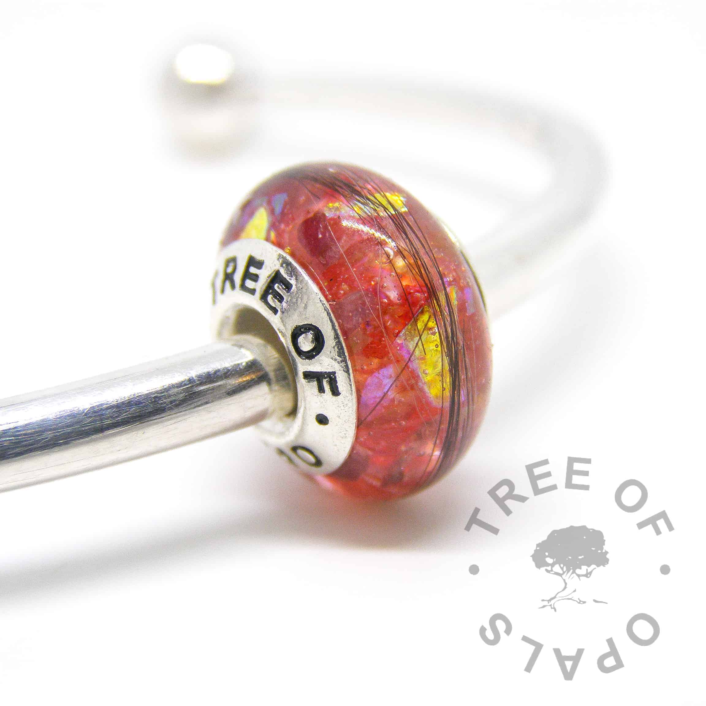 lock of hair charm bead in resin, ruby July birthstone, red opalescent flakes and genuine gold leaf guilded centre with a solid sterling silver Tree of Opals branded core