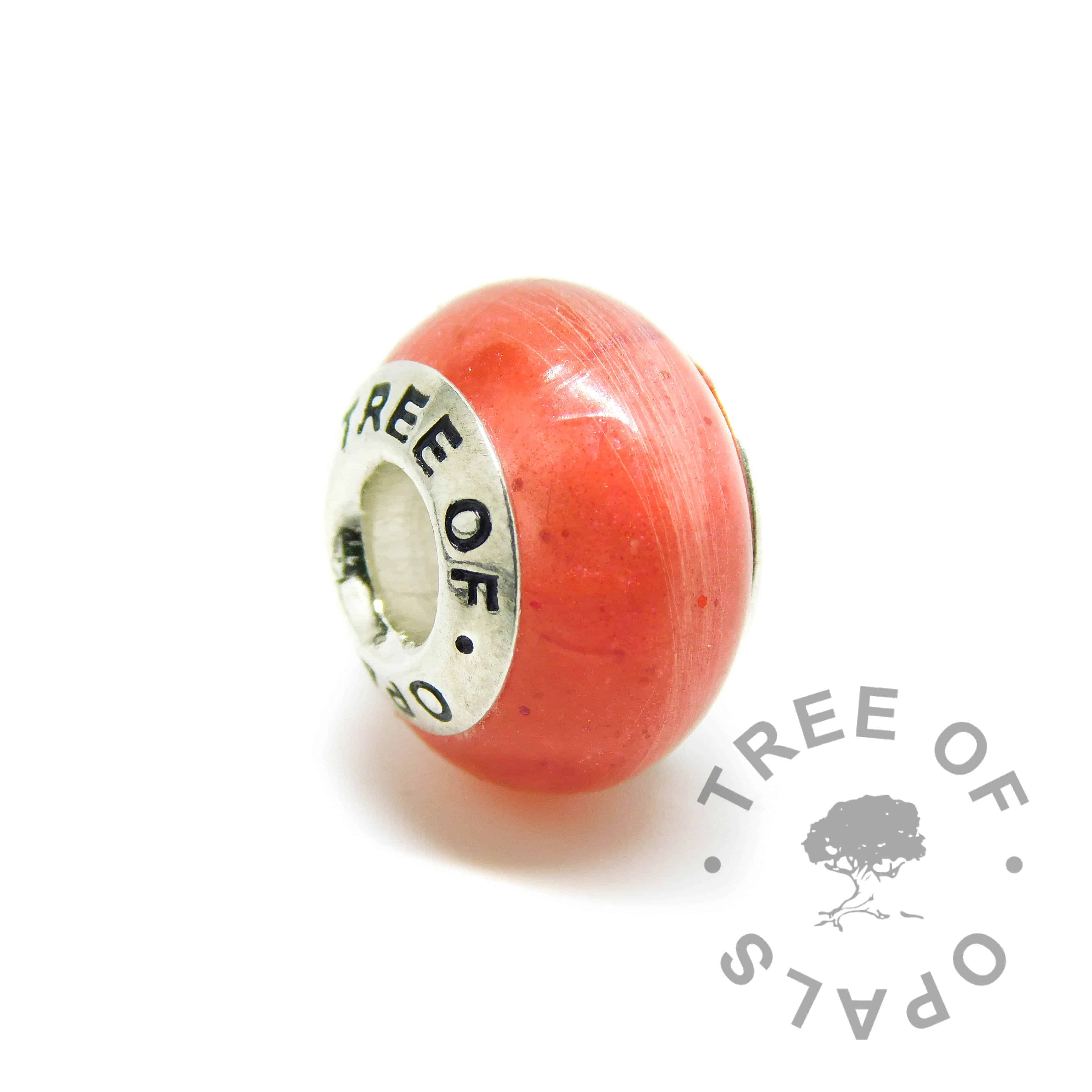 Lock of hair charm. Naturally white or very light blonde hair with dragon's blood red resin sparkle mix, no birthstones. Charm set with Tree of Opals core. Watermarked copyright image by Tree of Opals