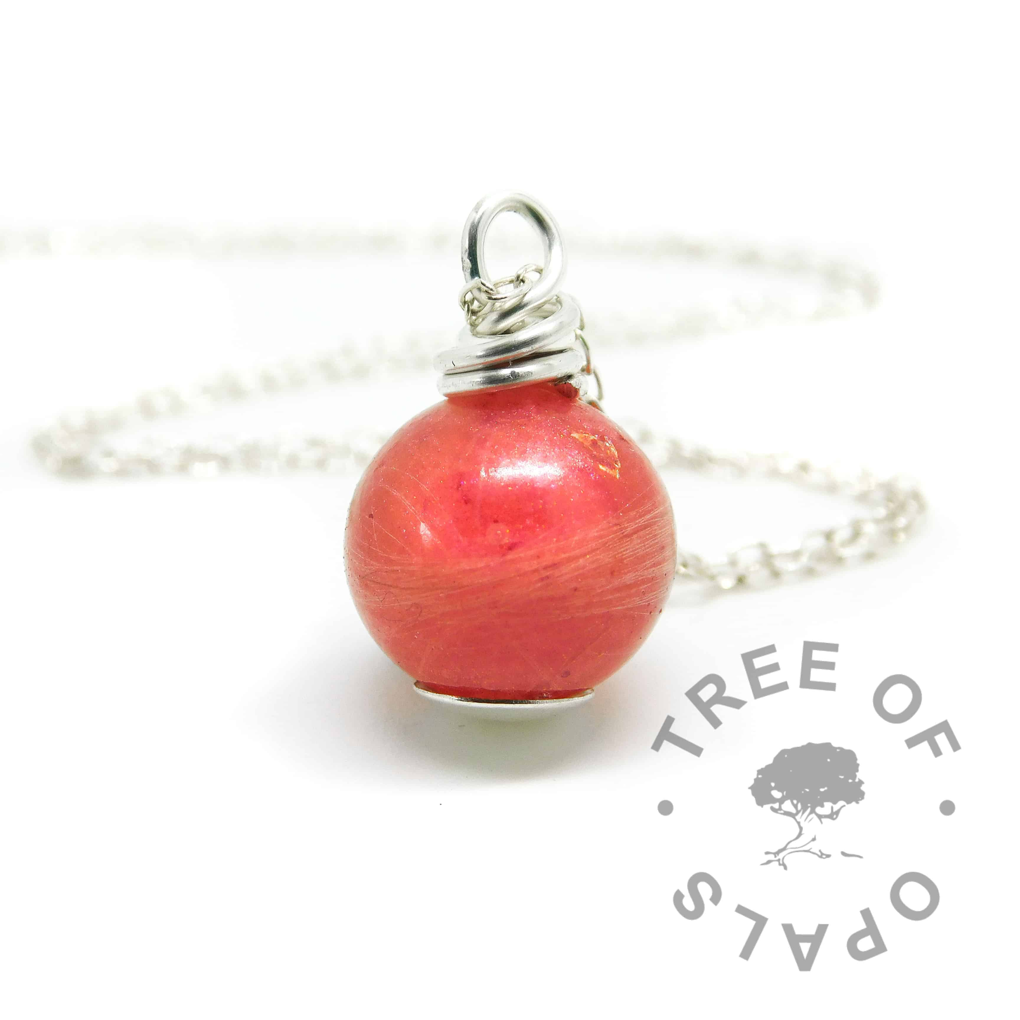 Lock of hair pearl. Naturally white or very light blonde hair with dragon's blood red resin sparkle mix, no birthstone. Set with solid sterling handmade headpin and shown with the standard necklace chain. Watermarked copyright image by Tree of Opals
