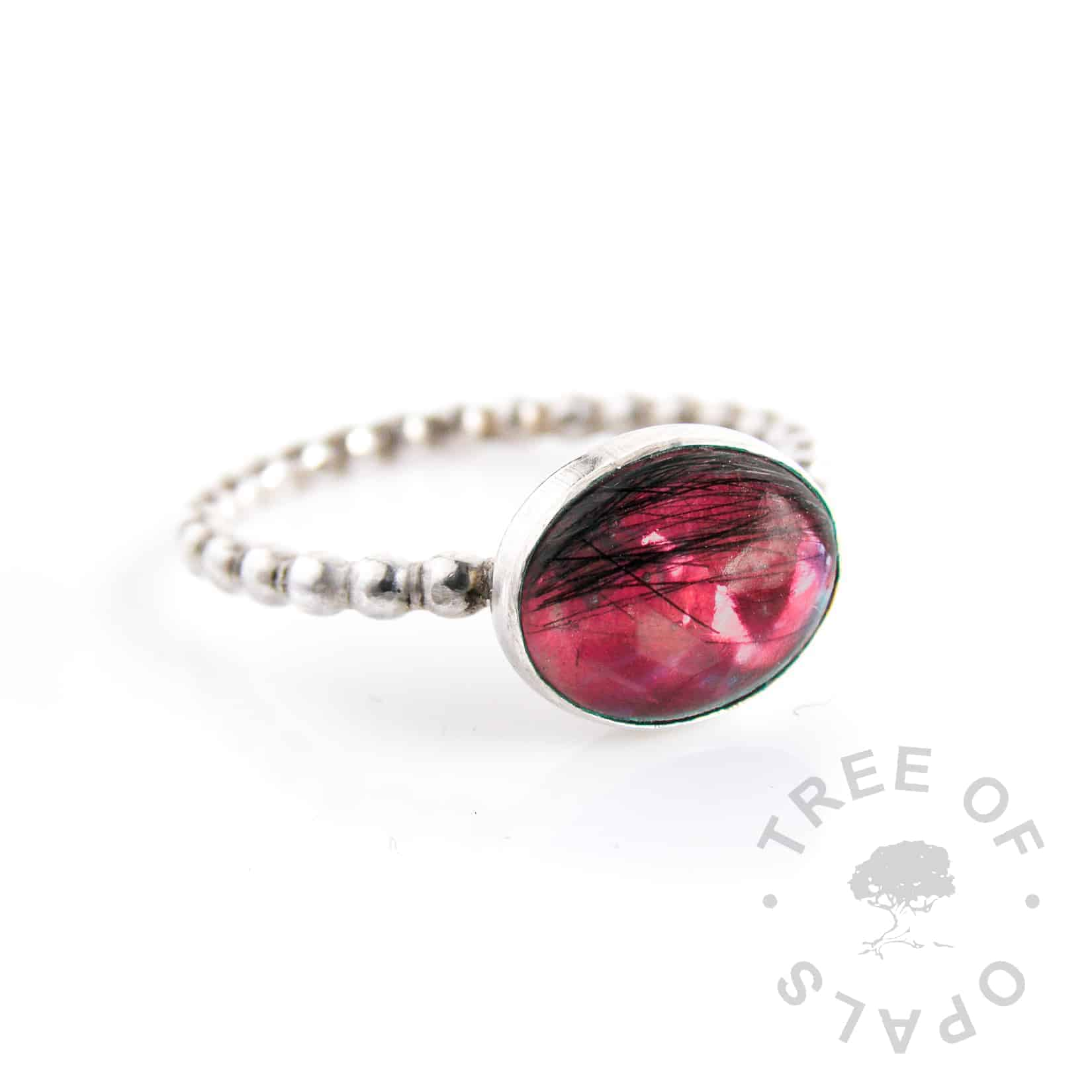 lock of hair ring with red opalescent flakes background on a bubble wire solid silver band and 10x8mm oval cabochon