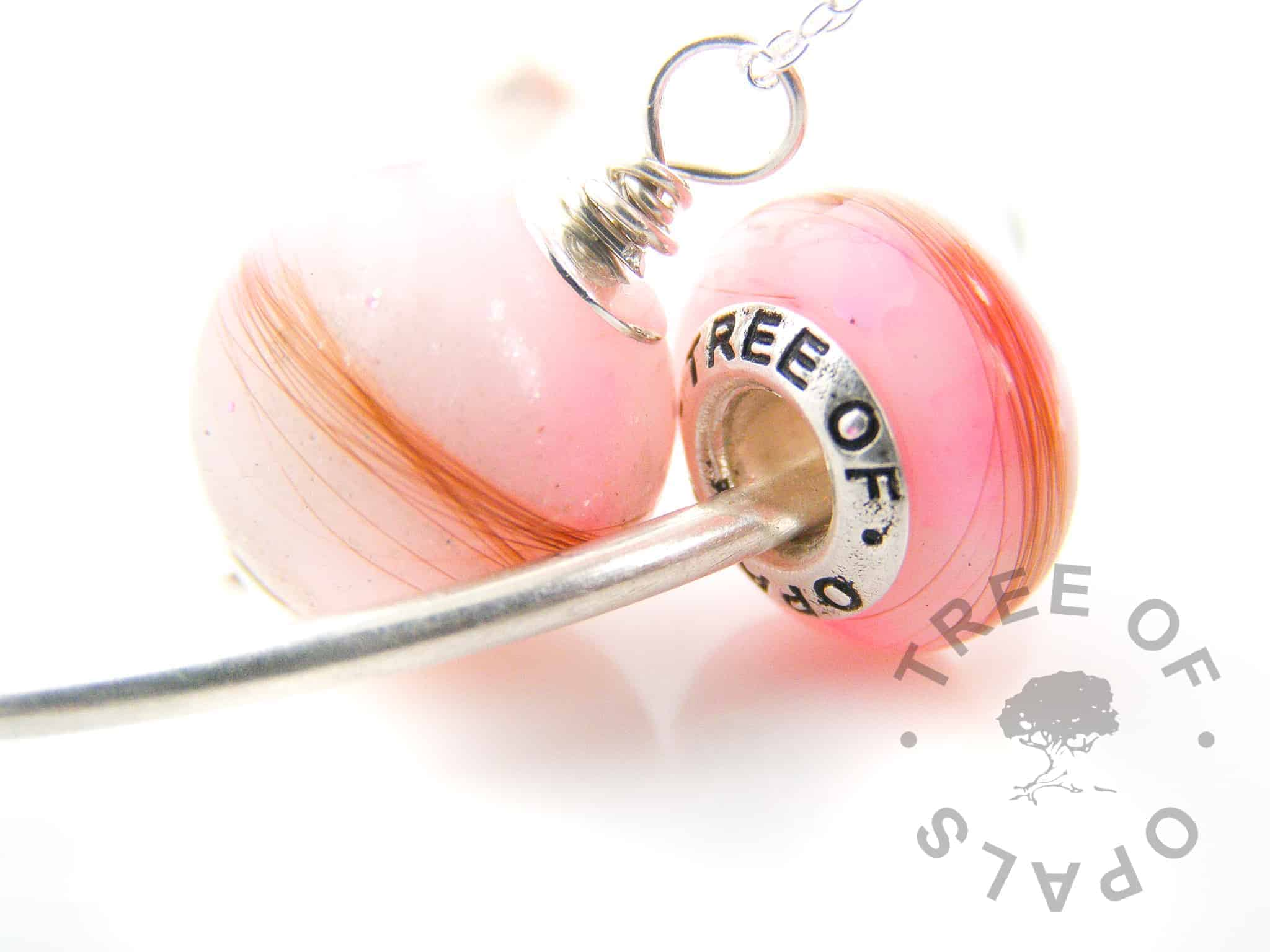 breastmilk charm and pearl set with pink and diamond, the pearl has diamond powder and the charm has a snow diamond. Lock of hair pearl and lock of hair charm pink opalescent flakes