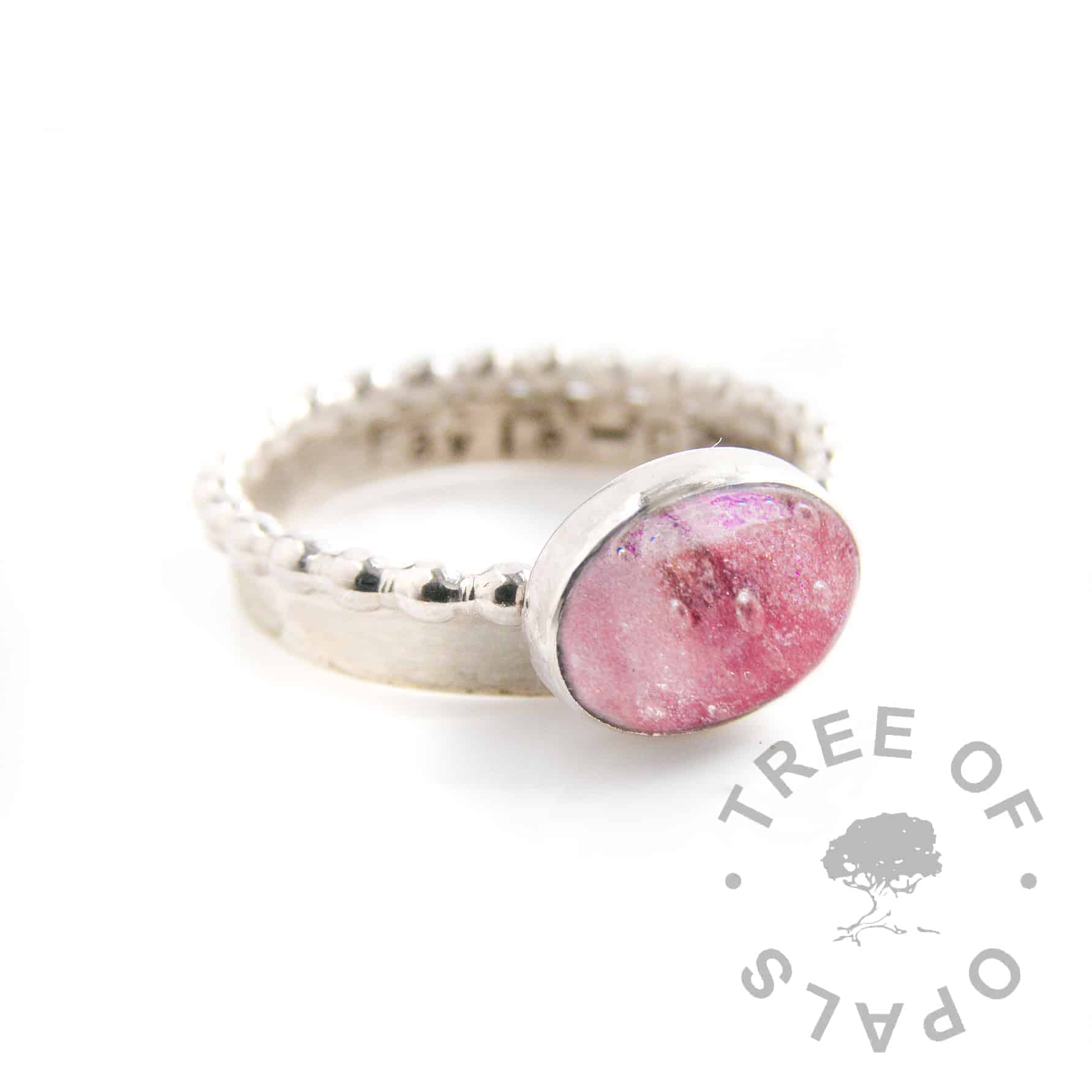 umbilical cord ring pink shimmer with ruby July birthstone, on a bubble wire band stacked with a brushed wire stamped stacking ring