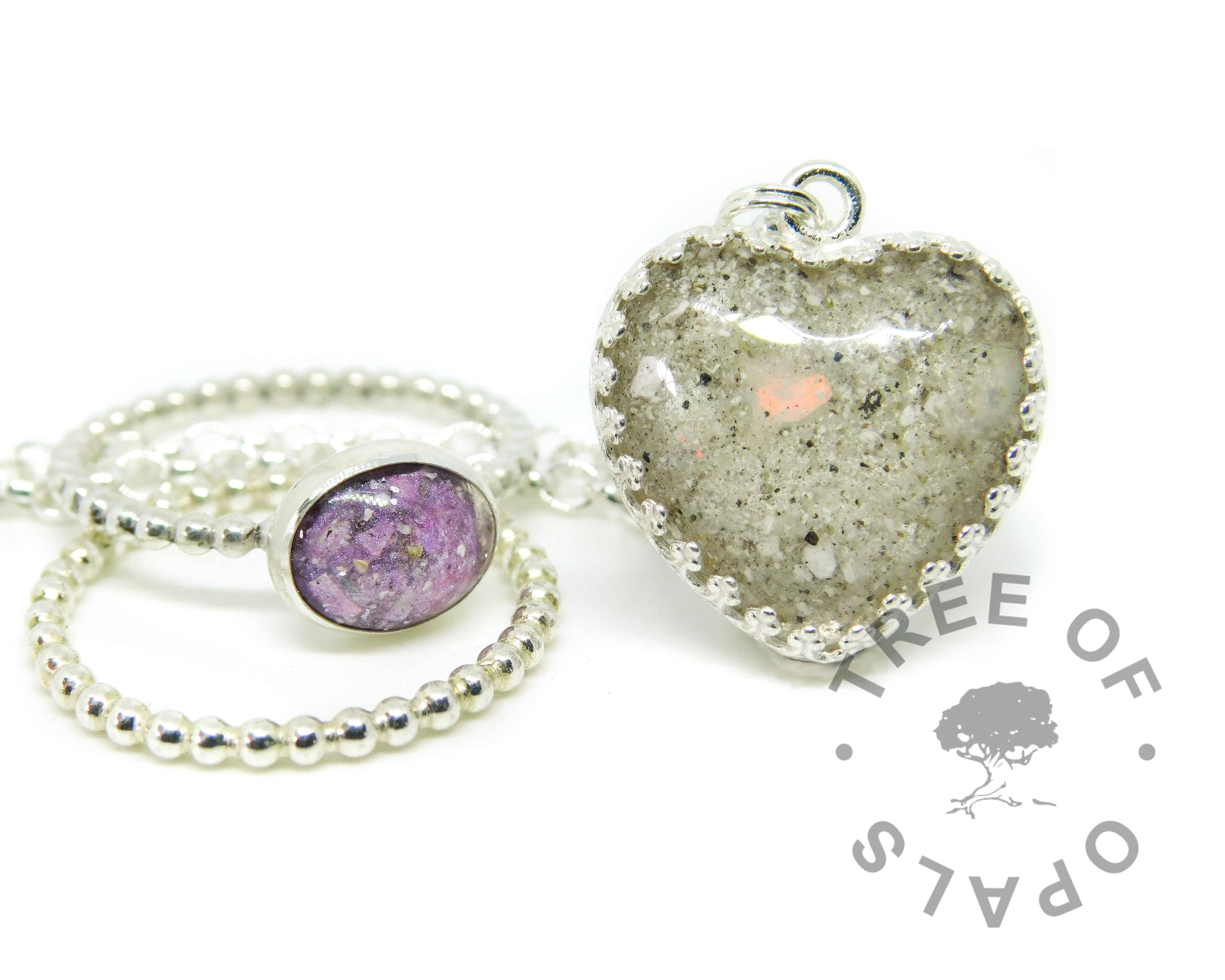 purple cremation ash ring, stacking ring and classic opal heart. Cremation ashes with orchid purple resin sparkle mix, set in a 10x8mm cabochon on a bubble wire band, with a bubble wire stacking ring. Cremation ash and clear resin with October birthstone genuine opal slices. Shown on a medium classic chain upgrade. Watermarked copyright image by Tree of Opals
