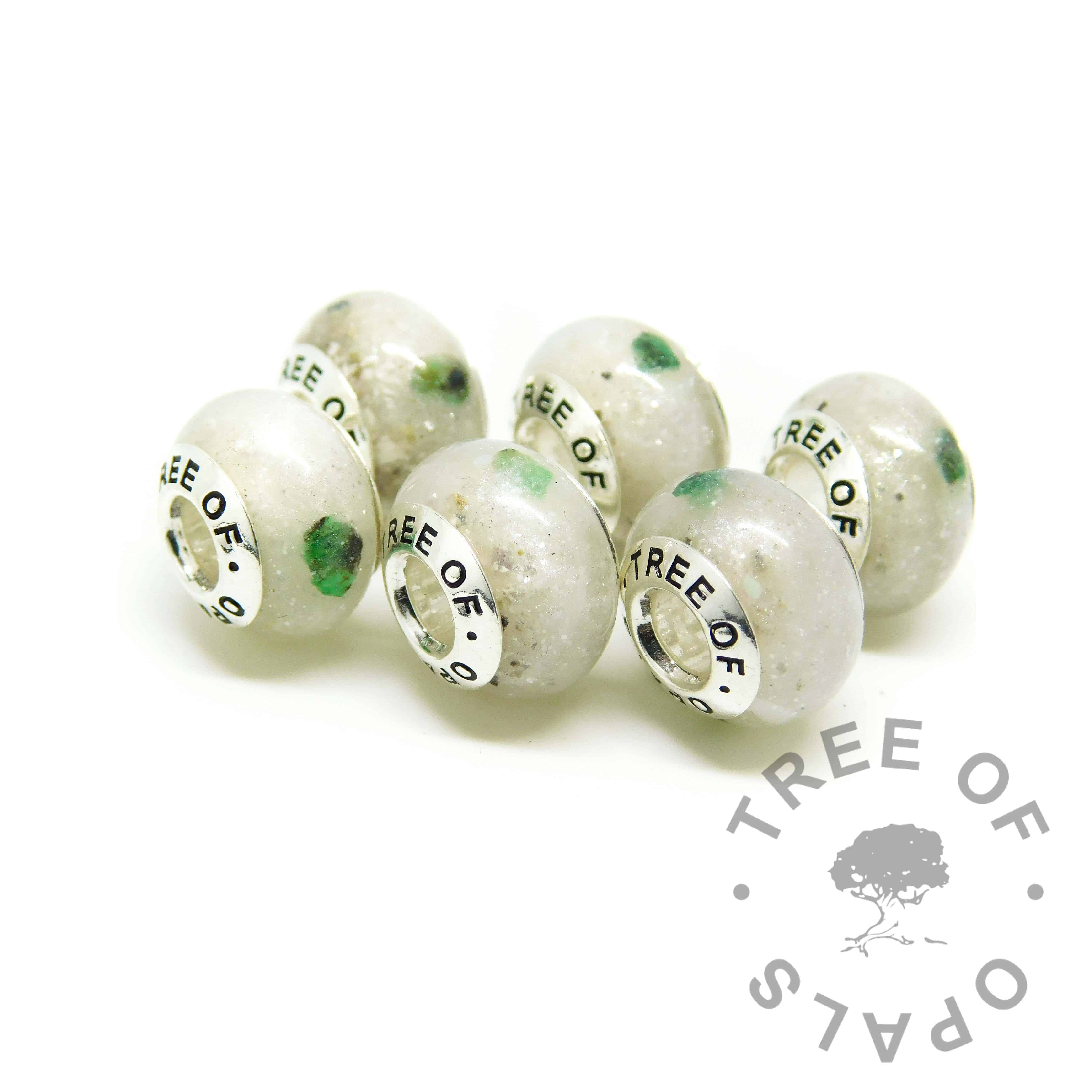 six cremation ash charms set with unicorn white resin sparkle mix and May birthstone rough natural emerald