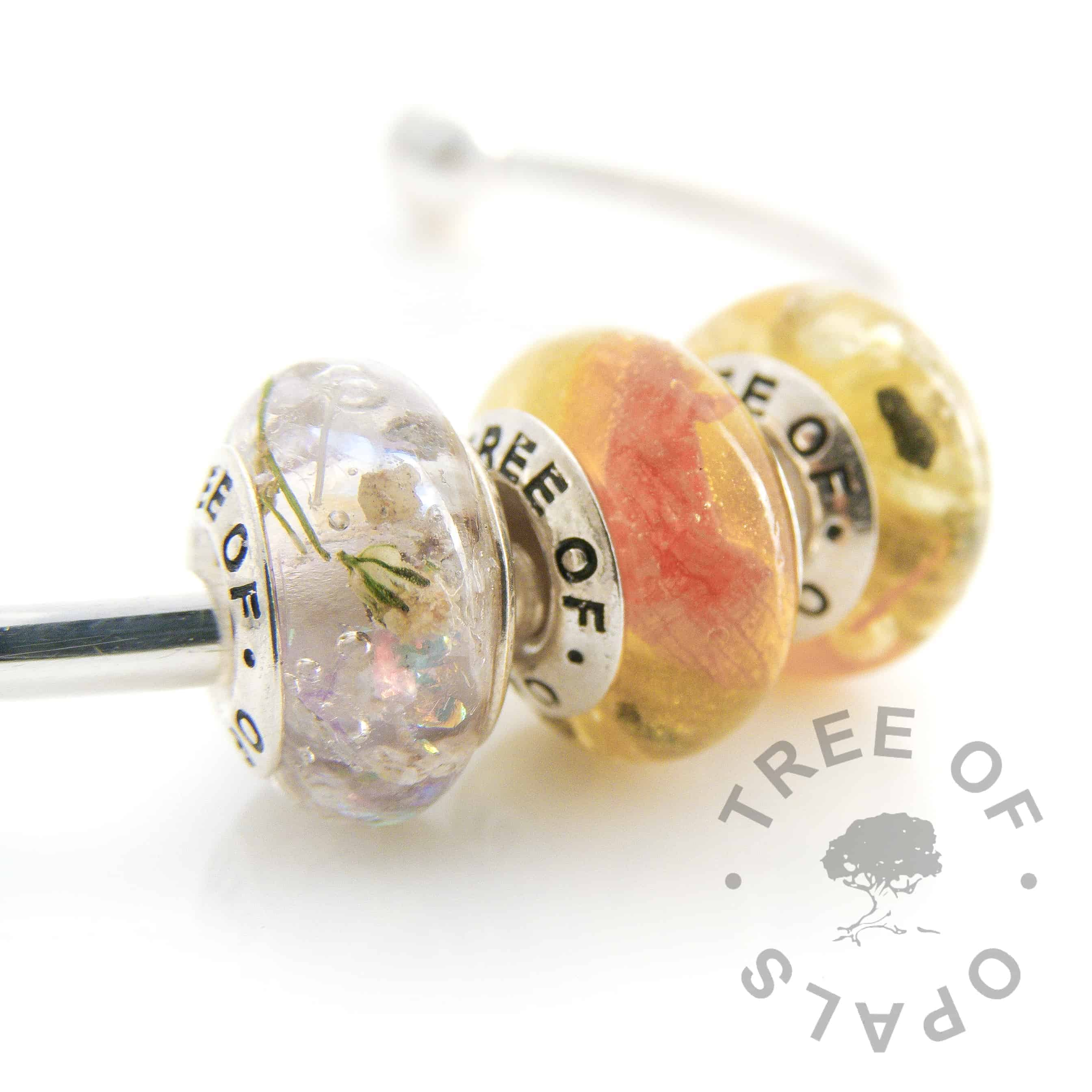 cremation ashes and flower charm trio with purple opalescent flakes, gypsophelia and sapphire September birthstone with cremation ash, and a yellow shimmer powder charm with daffodil petals, sapphire September birthstone with cremation ash x2. Solid sterling silver signature Tree of Opals core