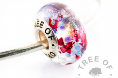lock of hair charm red flakes and blue opalescent. Hair bead with solid sterling silver Tree of Opals core