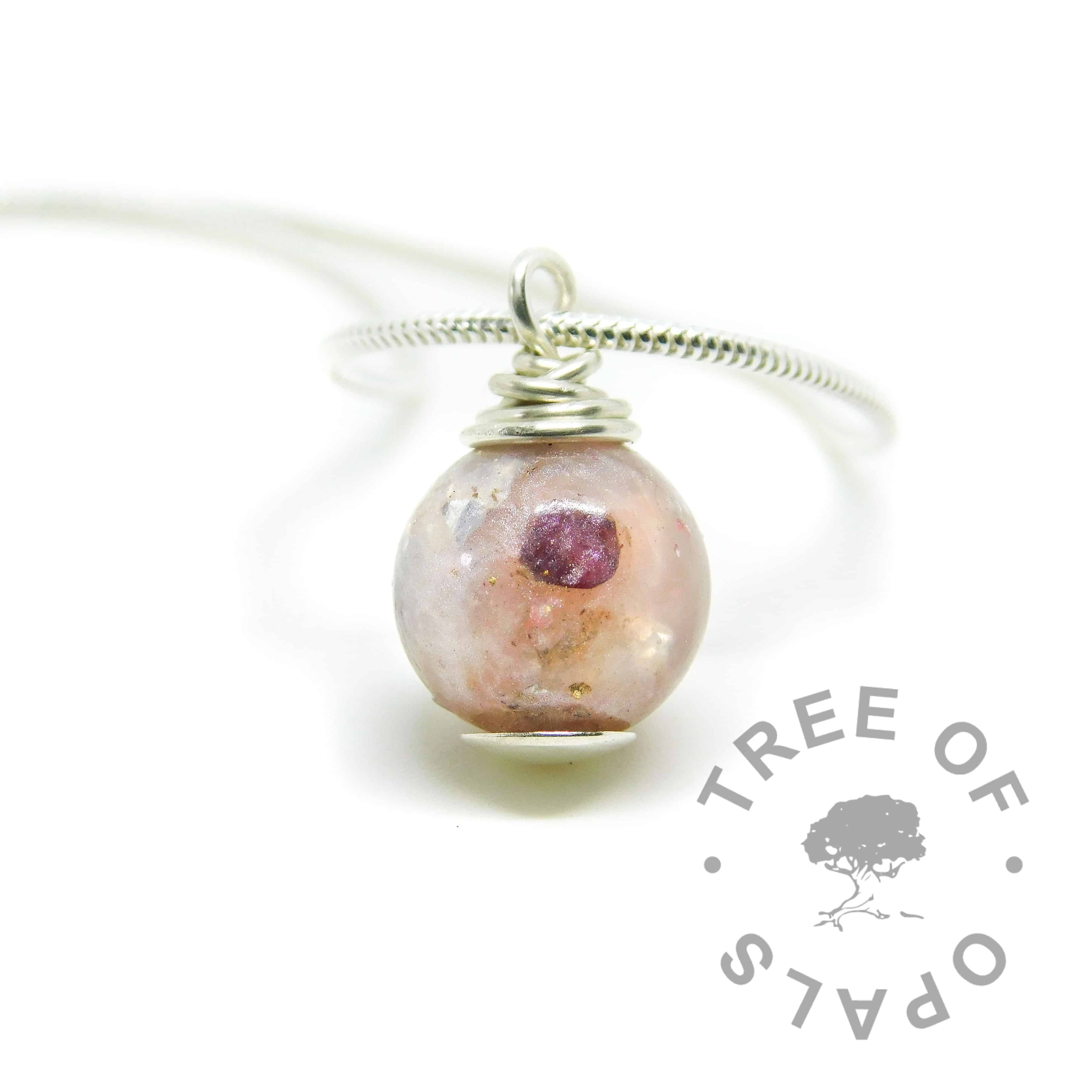 Umbilical cord pearl. Placenta umbilical cord with fairy pink resin sparkle mix, January birthstone red garnet, silver and gold leaf. Set with solid sterling handmade headpin and shown with a light snake chain necklace upgrade. Watermarked copyright image by Tree of Opals