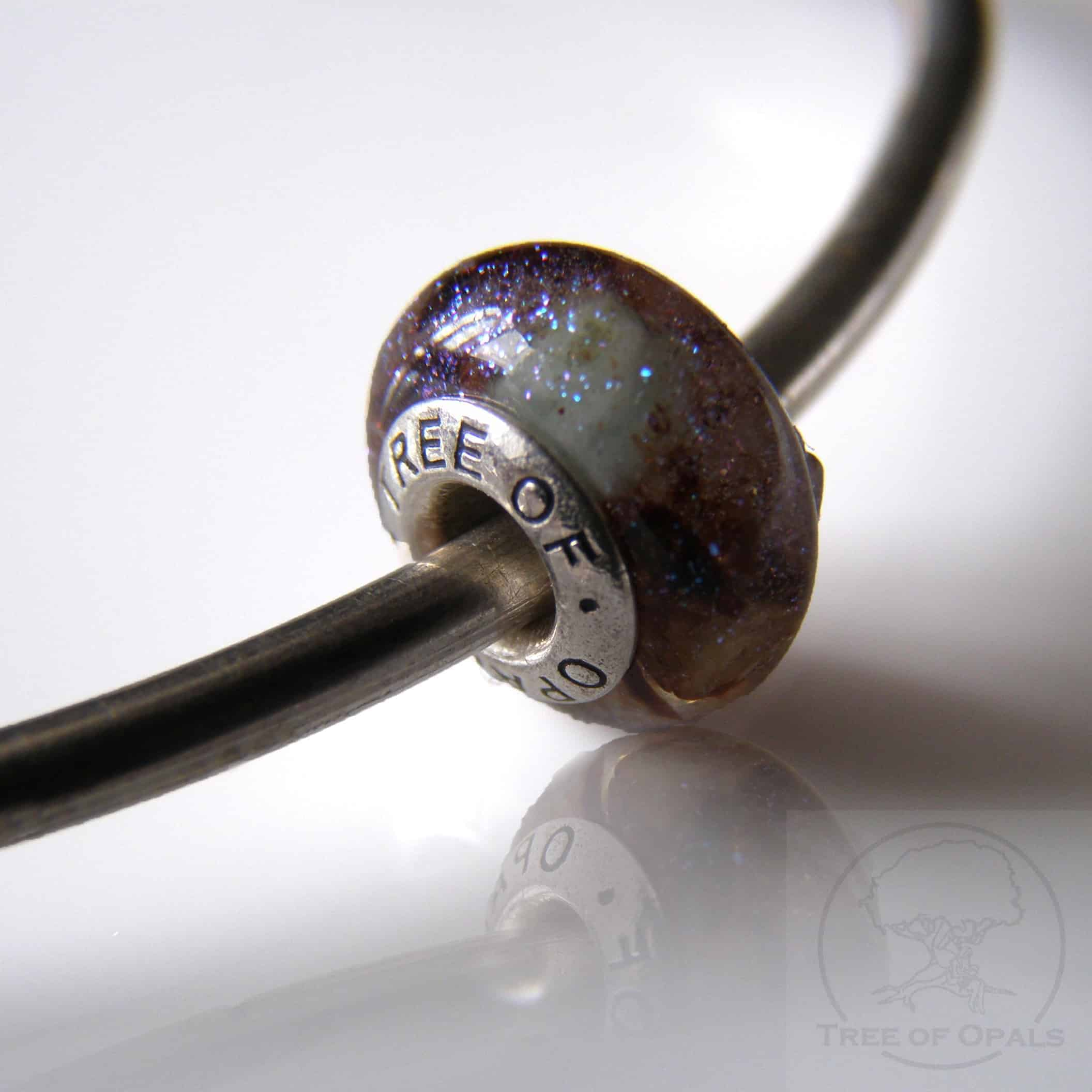 Umbilical cord charm that fits right onto Pandora bracelets, featuring irridescent sparkles and natural emerald
