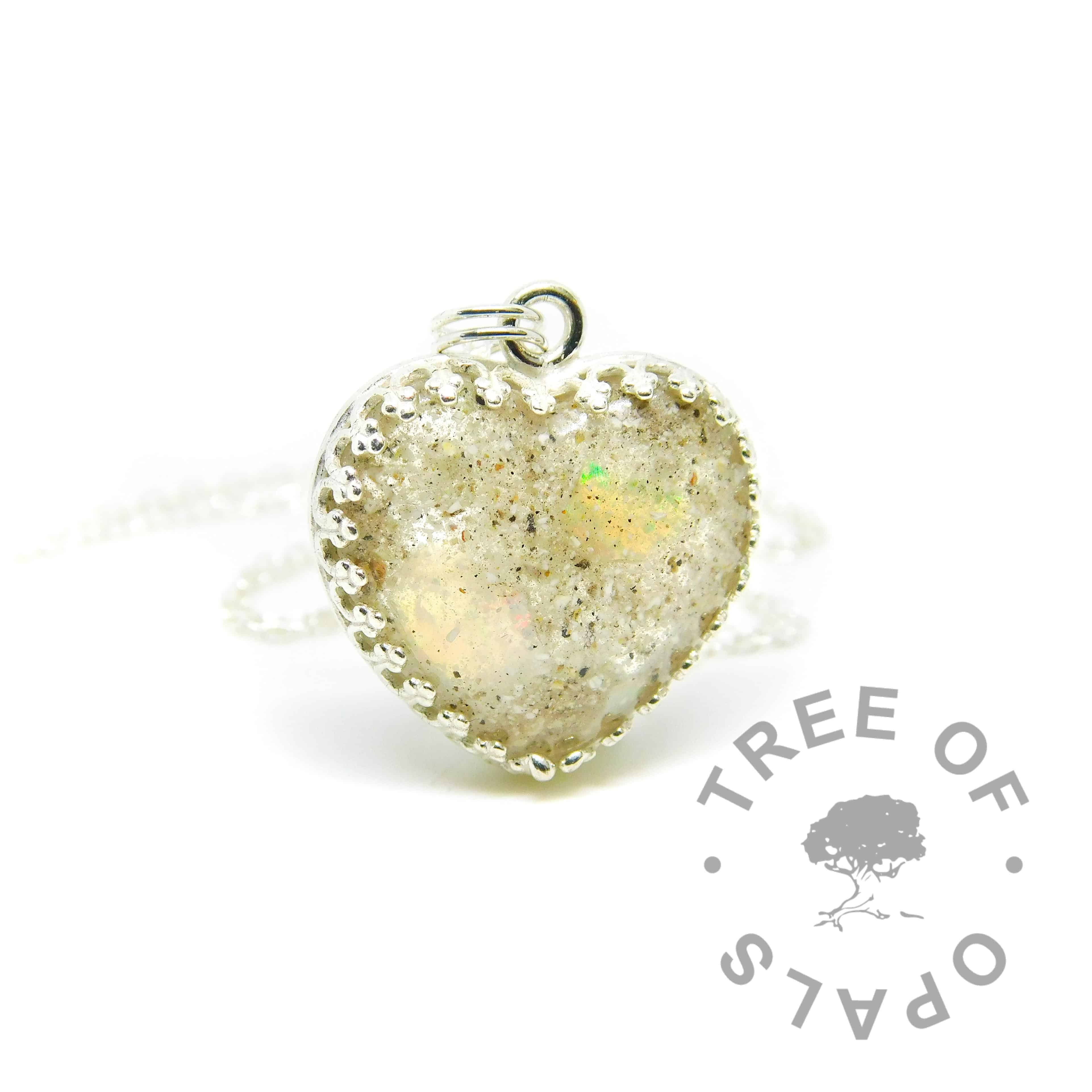 Classic cremation ash heart necklace with clear resin (no sparkle mix), rough natural opal slices October birthstone. Solid sterling silver 20mm crown point heart setting (925 stamped on the back). Light medium classic chain necklace upgrade shown (sold separately). Watermarked copyright Tree of Opals memorial jewellery image