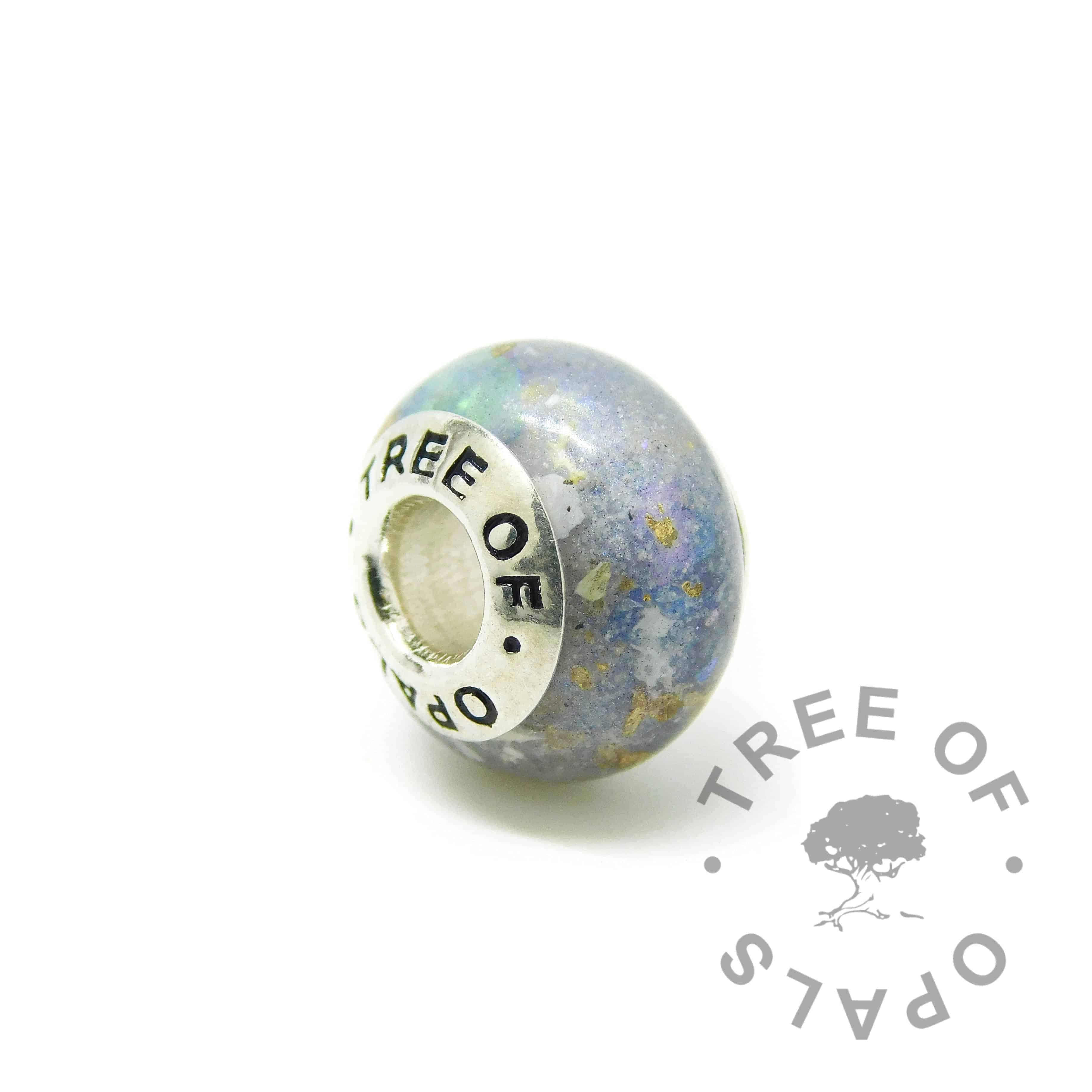 Cremation ash charm with Aegean blue resin sparkle mix, genuine rough natural opal slices October birthstone. Solid sterling silver Tree of Opals signature core (925 stamped on the back). Watermarked copyright Tree of Opals memorial jewellery image