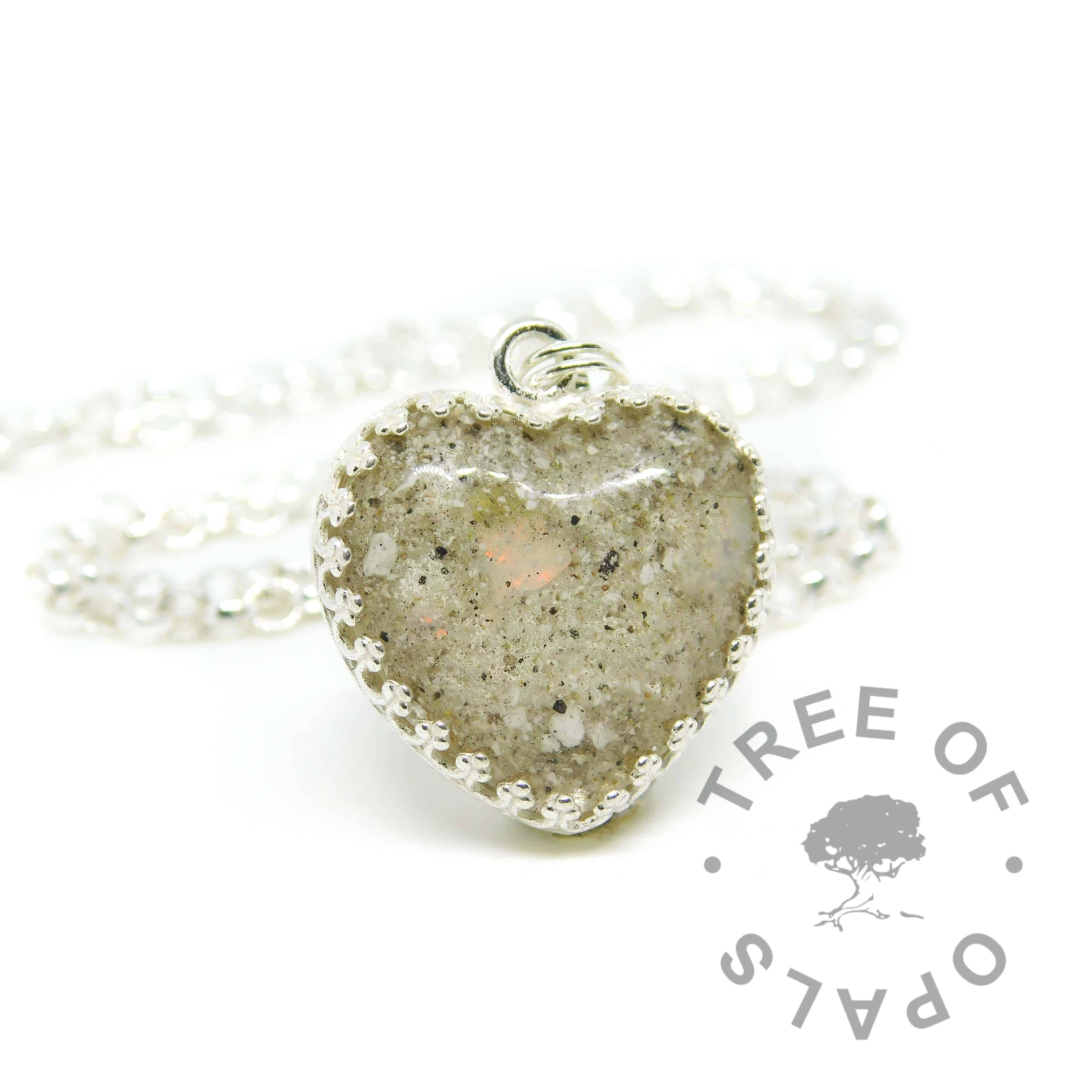 Cremation ashes with crystal clear resin, set in an 18mm heart cabochon and genuine October birthstone opal slices, in a solid sterling silver crown setting. Shown on a medium classic chain upgrade. Watermarked copyright image by Tree of Opals