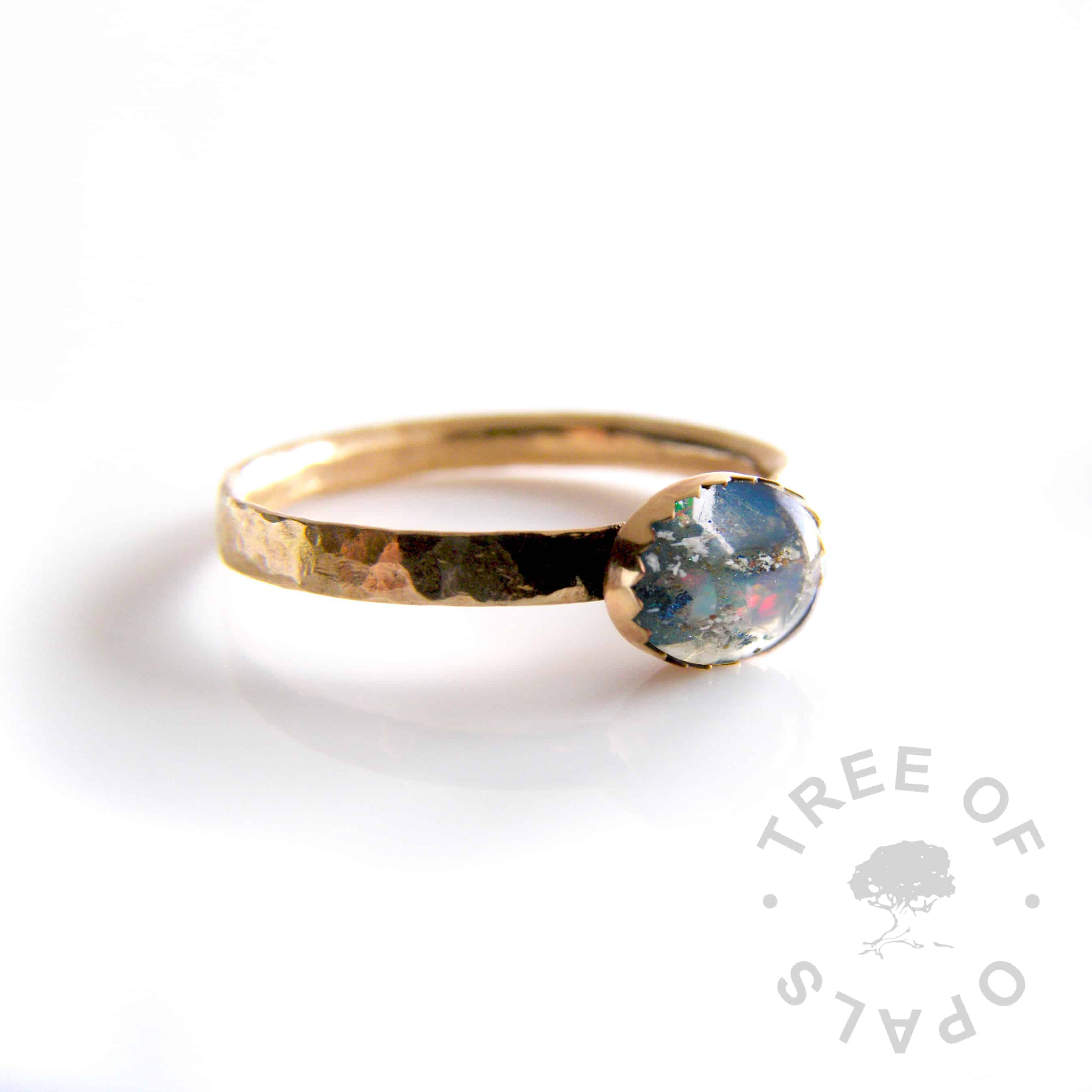 (mockup) solid 14ct yellow gold cremation ash ring with genuine opal flakes and Aegean blue shimmer, textured comfort fit band and serrated 8x6mm cabochon handmade by goldsmith Nic Kamminga, hallmarked with our maker's mark at the Birmingham Assay Office