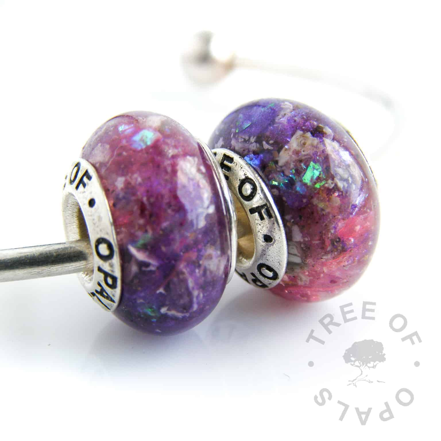 cremation ash charm duo, with red garnet (January birthstone) two beads with cremains, pink and purple opalescent flakes and violet and indigo shimmer powder, set with solid sterling silver Tree of Opals signature cores. Perfect memorial gift