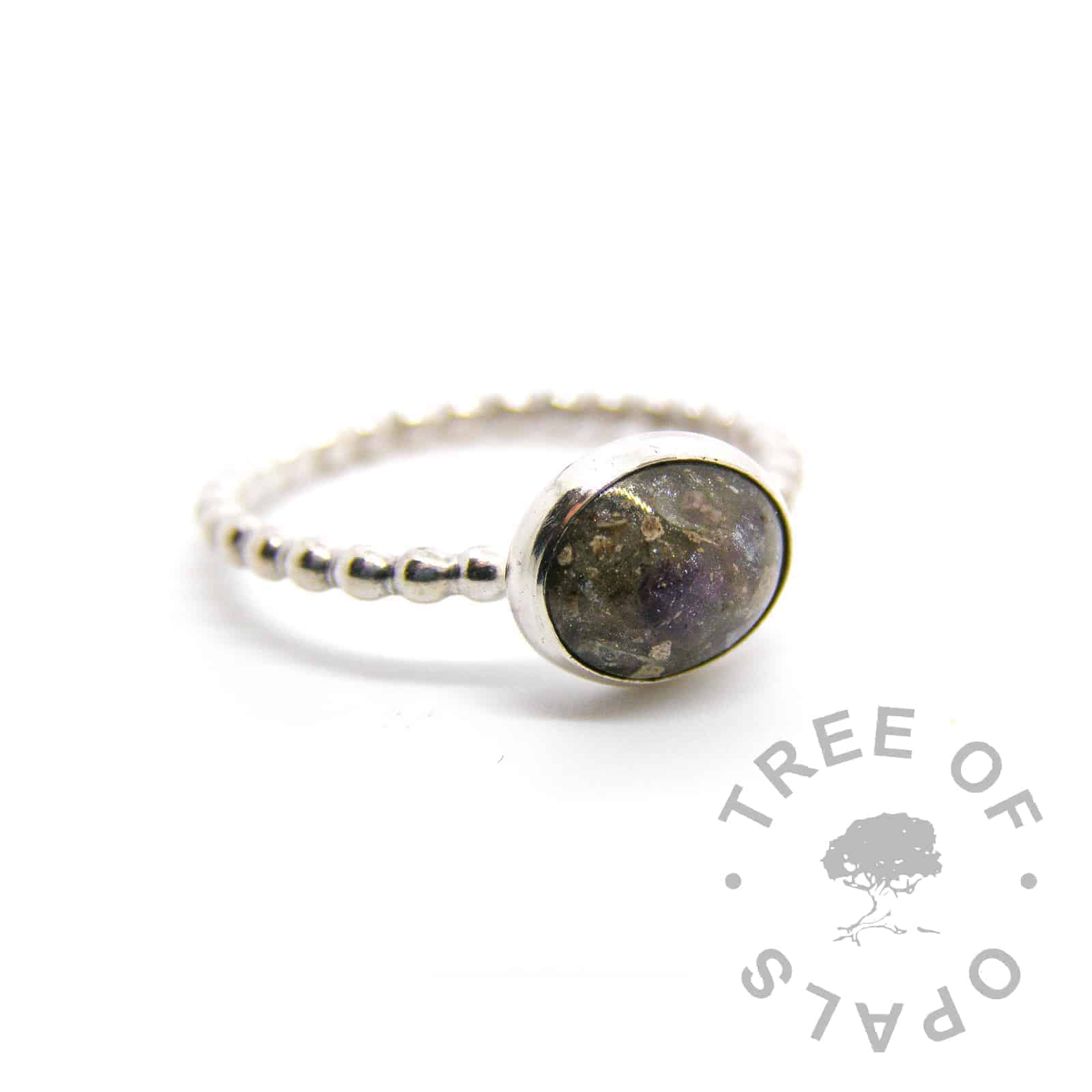solid sterling silver cremation ash ring with basilisk green sparkles and February birthstone amethyst, set in a 10x8mm cabochon on a bubble wire band