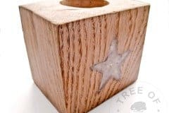 cremation ash candle holder with star shape, handmade from scratch with reclaimed oak. Shown with opalescent flakes
