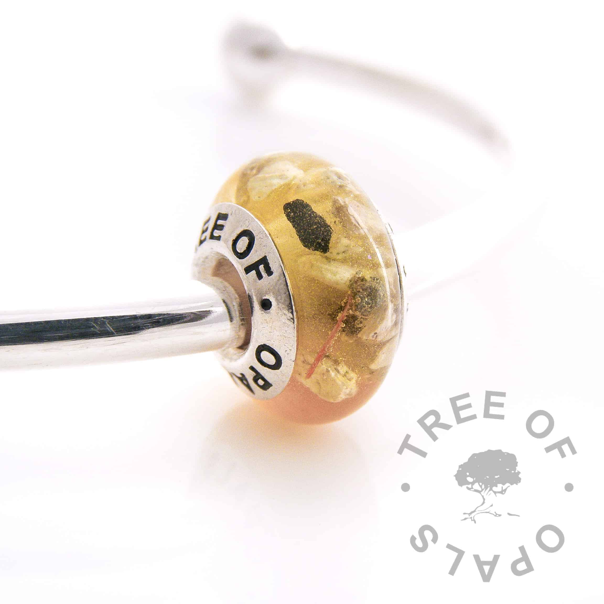 cremation ash and daffodil flower charm bead, daffodil petals with yellow shimmer powder subtle. Solid sterling silver signature Tree of Opals core