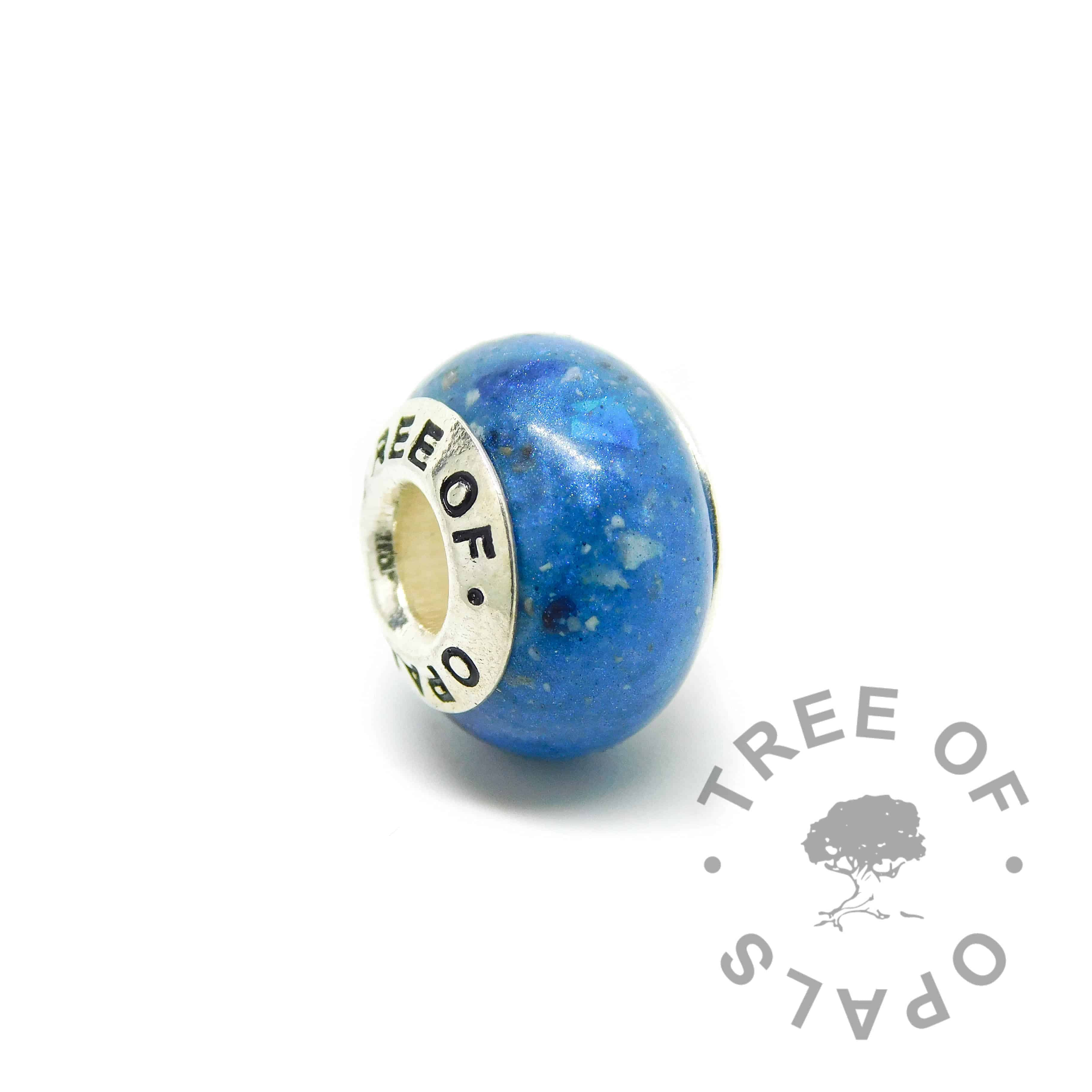 cremation ash charm with vivid blue resin sparkle mix, rough natural sapphire September birthstone. Solid sterling silver Tree of Opals signature core (925 stamped on the back). Watermarked copyright Tree of Opals memorial jewellery image