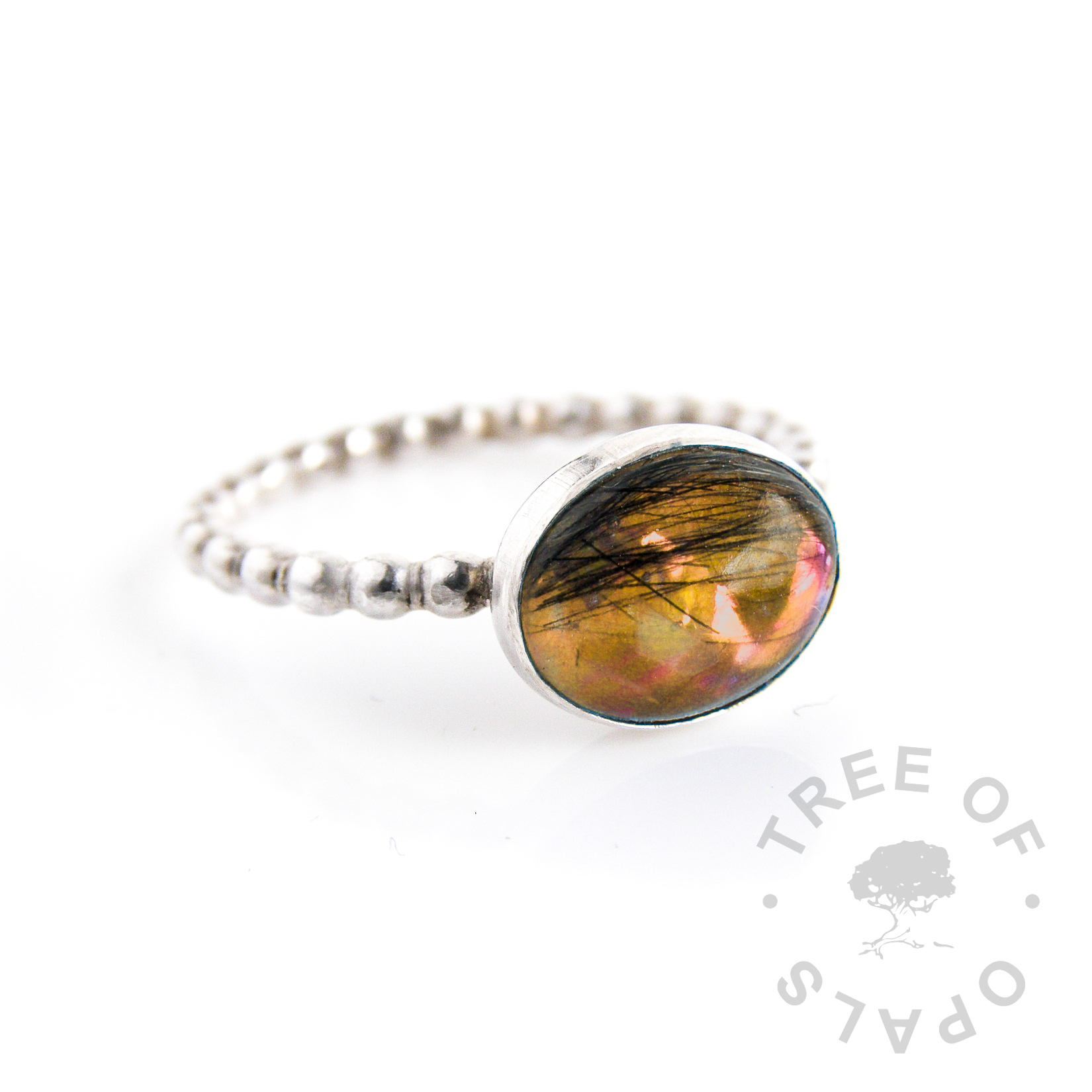lock of hair ring with orange opalescent flakes background on a bubble wire solid silver band and 10x8mm oval cabochon