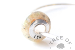 resin cremation ash charm with orange shimmers, showing the back of the charm