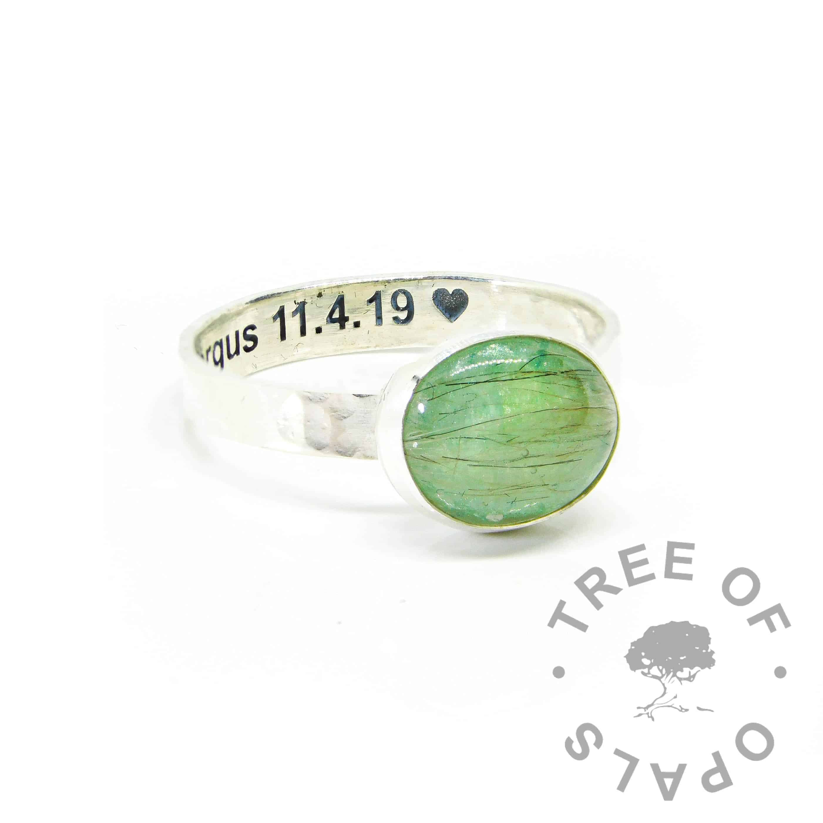 Fur ring on 3mm textured band with basilisk green resin sparkle mix. Engraved inside in arial font with heart emoji. Much of the fur is translucent and can't be seen, we only see the darker strands