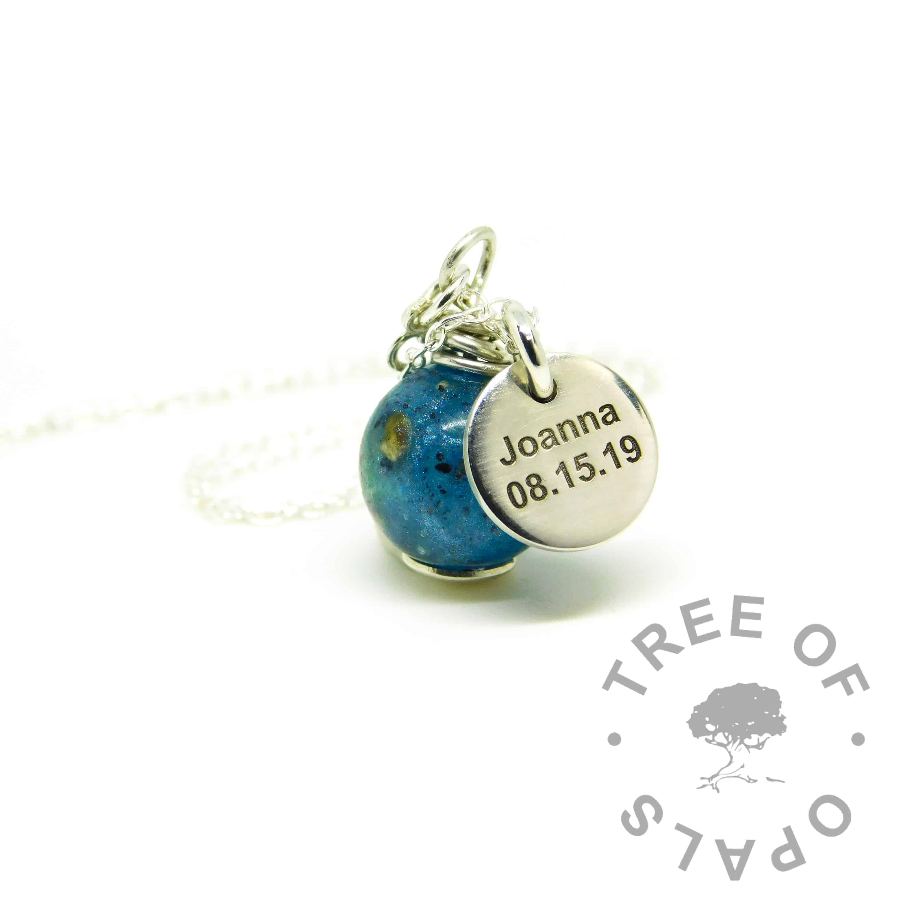 keepsake jewellery umbilical necklace with Aegean blue resin sparkle mix, shown with an engraved disc