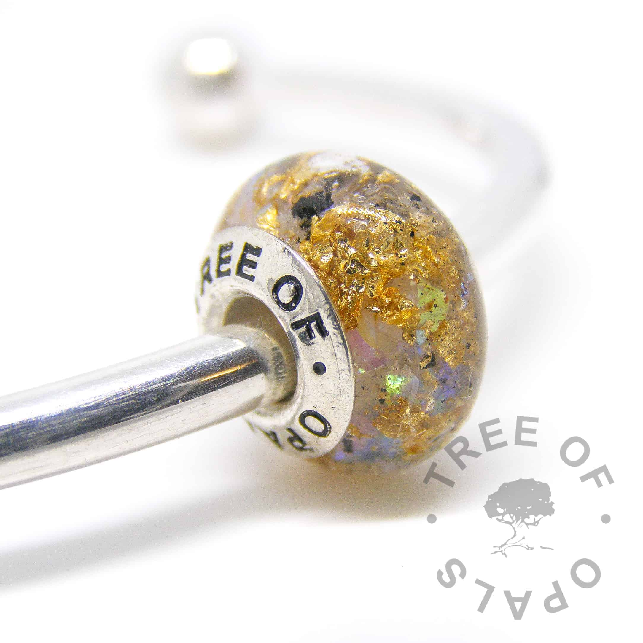 cremation ashes bead in resin, white opalescent and genuine gold leaf with a solid sterling silver Tree of Opals branded core cremation ash charm